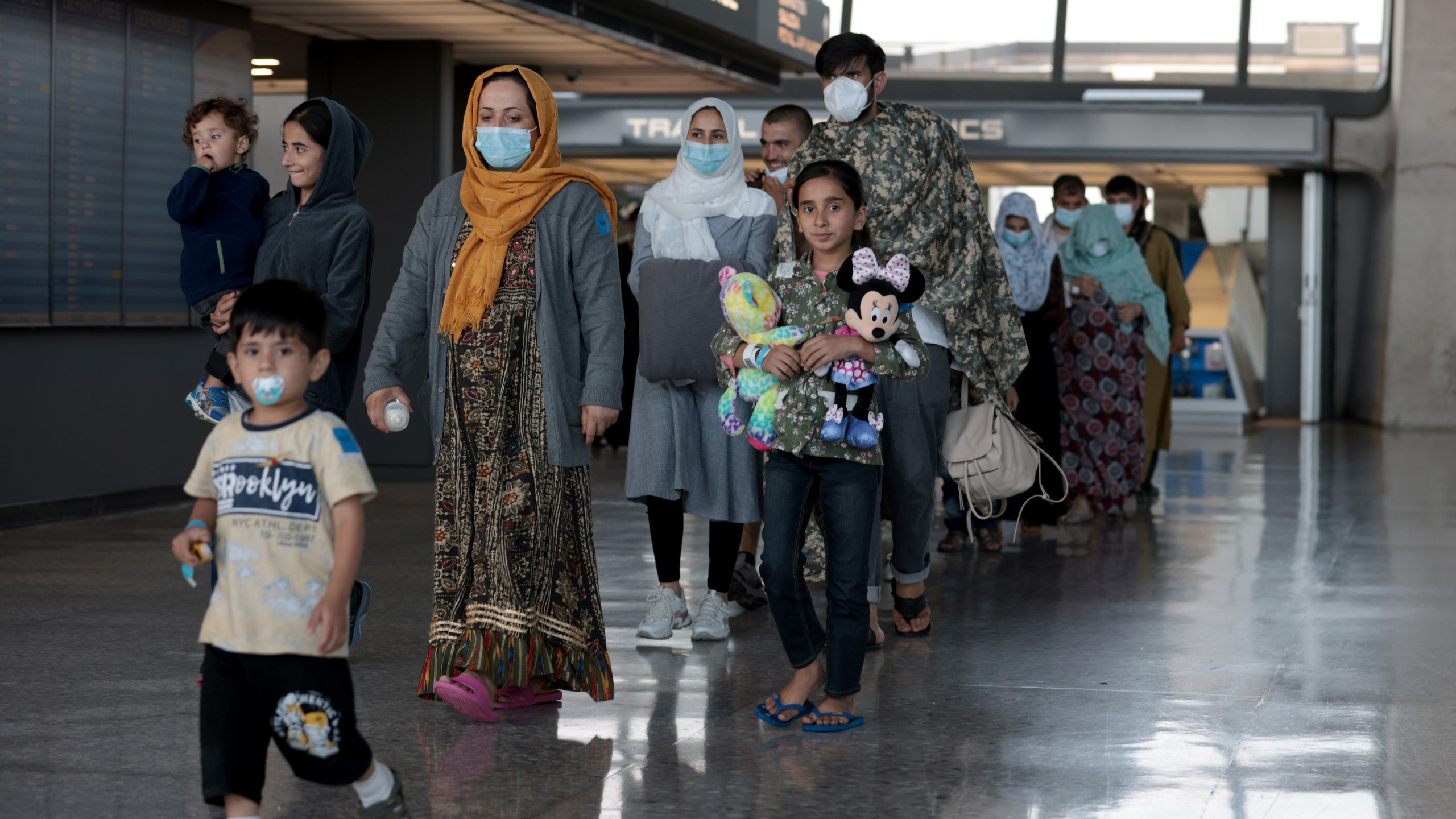 A family evacuated from Afghanistan is led through the arrival terminal at the Dulles International Airport to board a bus that will take them to a refugee processing center on Aug. 25, 2021 in Dulles, Virginia. (Anna Moneymaker/Getty Images)