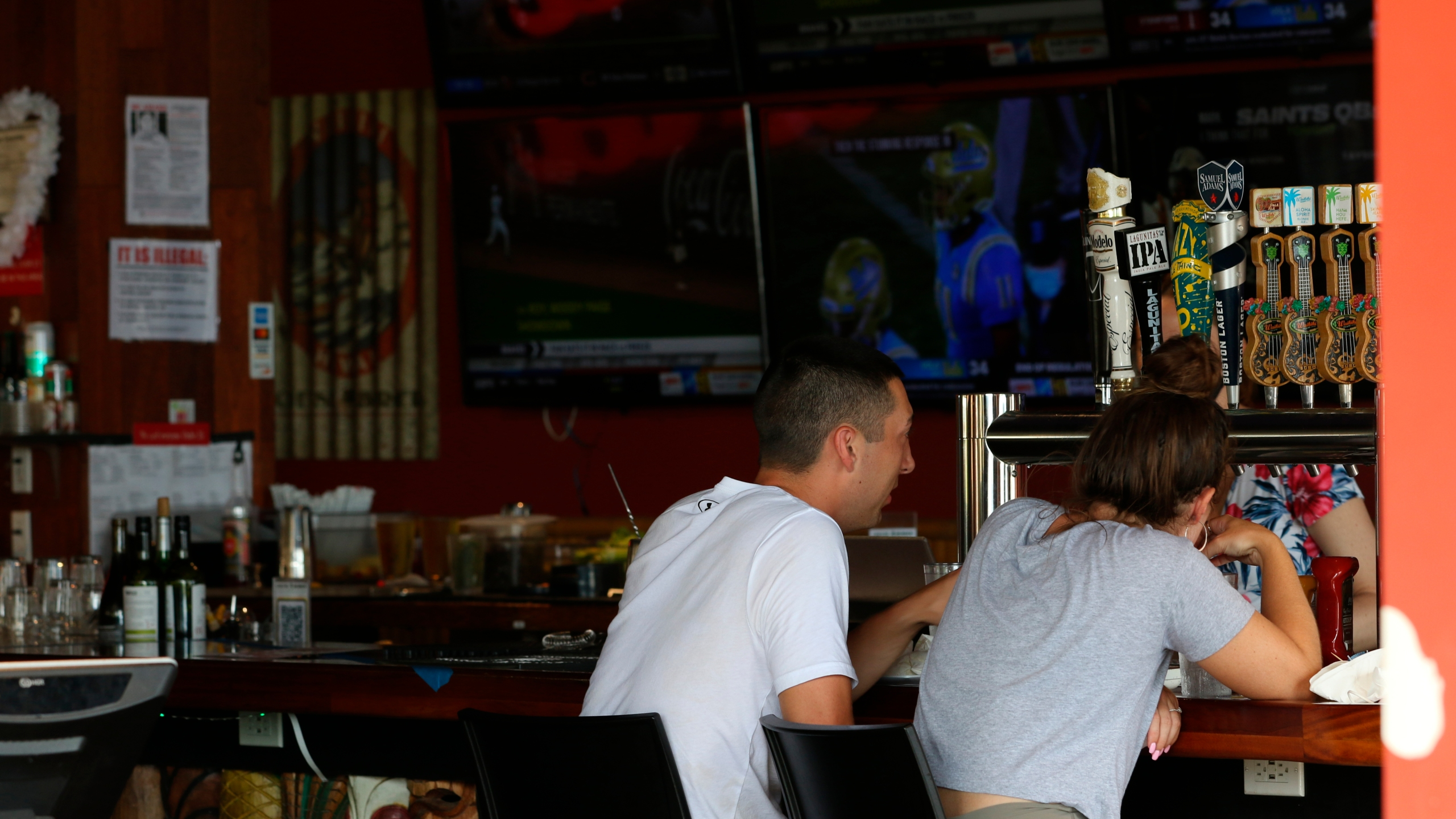 In this Aug. 24, 2021, photo, people sit at a Waikiki bar in Honolulu. The mayor of Honolulu says starting Sept. 13, 2021, the city will require patrons of restaurants, bars, museums, theaters and other establishments to show proof of vaccination or a recent negative test for COVID-19. (AP Photo/Caleb Jones)