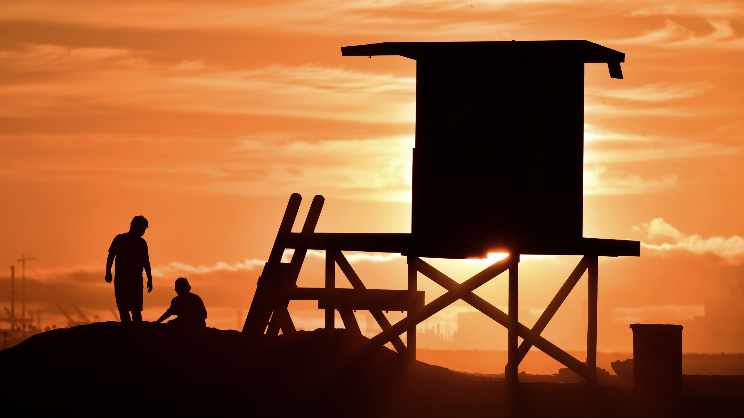 Children play beside a lifeguard tower as sunset approaches at Sunset Beach in Huntington Beach on July 21, 2018. (Frederic J. Brown/AFP via Getty Images)