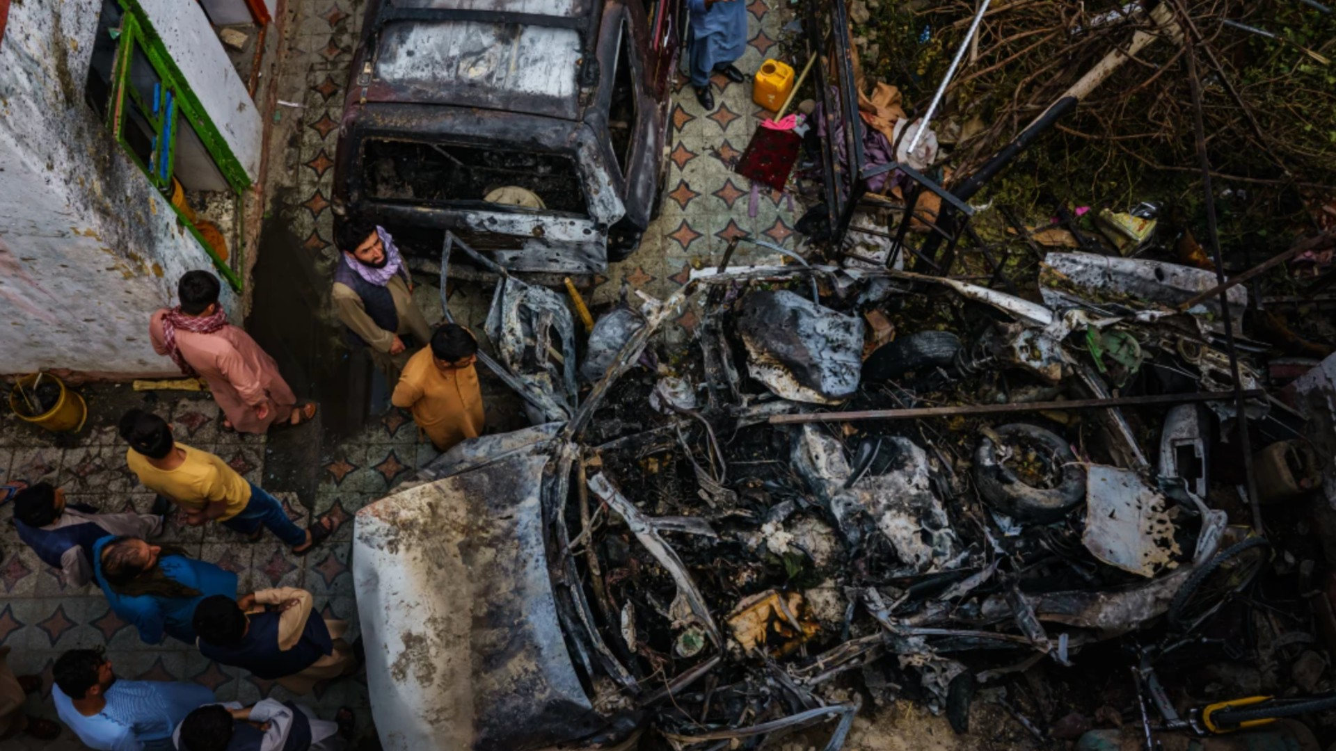 Relatives and neighbors of the Ahmadi family gather around a burned-out vehicle that the family says was hit by a U.S. drone strike, killing 10 people.(Marcus Yam / Los Angeles Times)