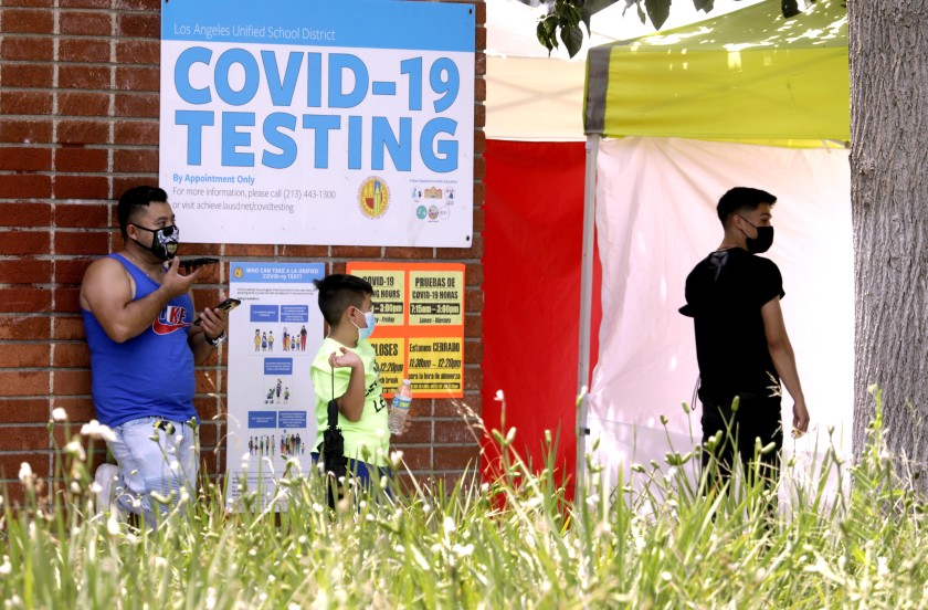 A father waits with his son to be tested for the coronavirus at Northridge Middle School in Northridge in this undated photo. (Genaro Molina/Los Angeles Times)