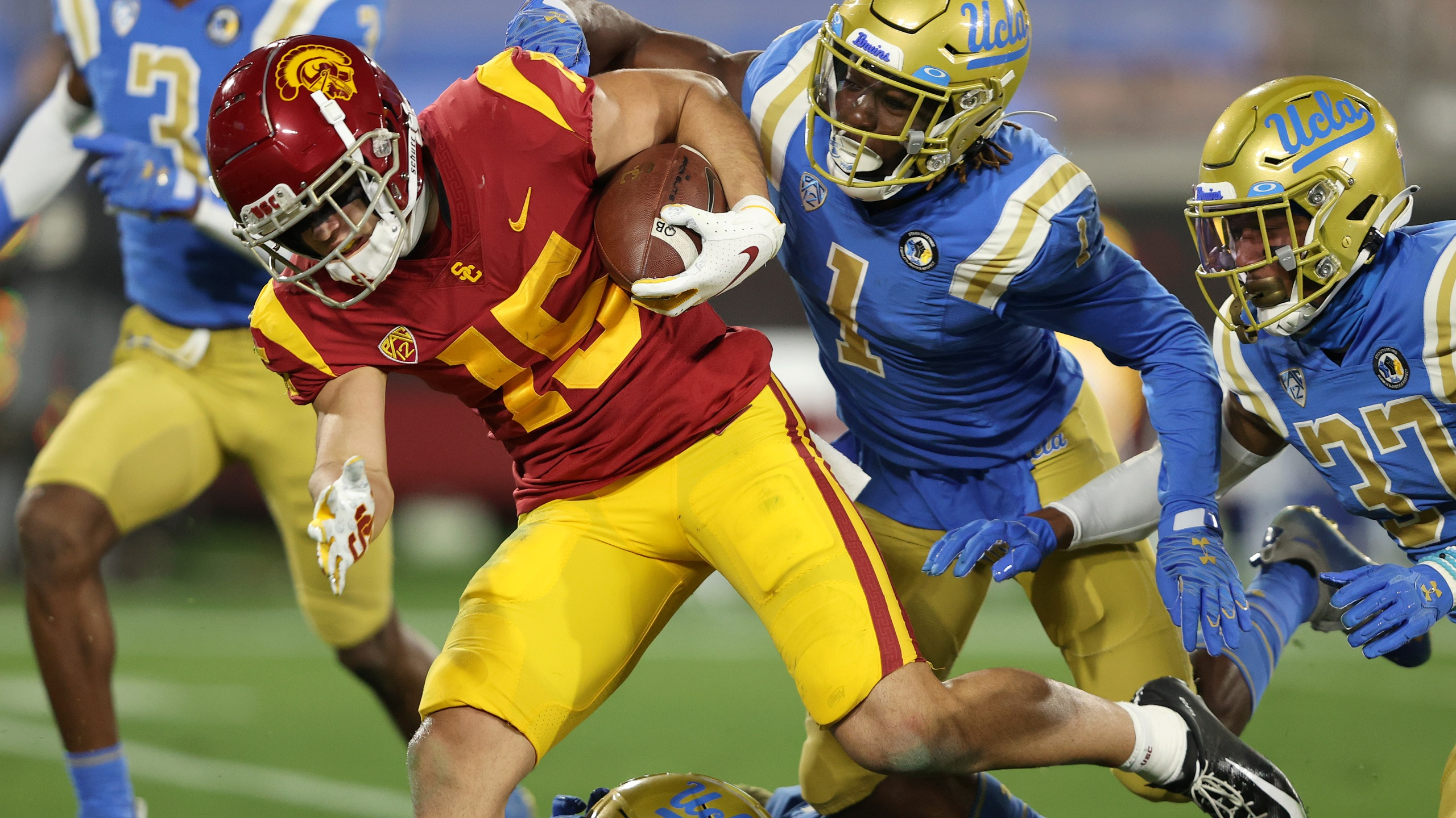Drake London of the USC Trojans runs past Jay Shaw and Quentin Lake of the UCLA Bruins for a touchdown during the first half of a game at the Rose Bowl on Dec. 12, 2020 in Pasadena, California. (Sean M. Haffey/Getty Images)