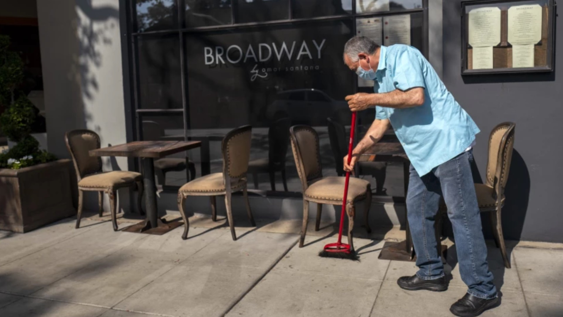 Javier Garcia wears a mask in Laguna Beach while sweeping outside Broadway by Amar Santana in May. Orange County has seen a surge in coronavirus cases this summer.(Francine Orr / Los Angeles Times)