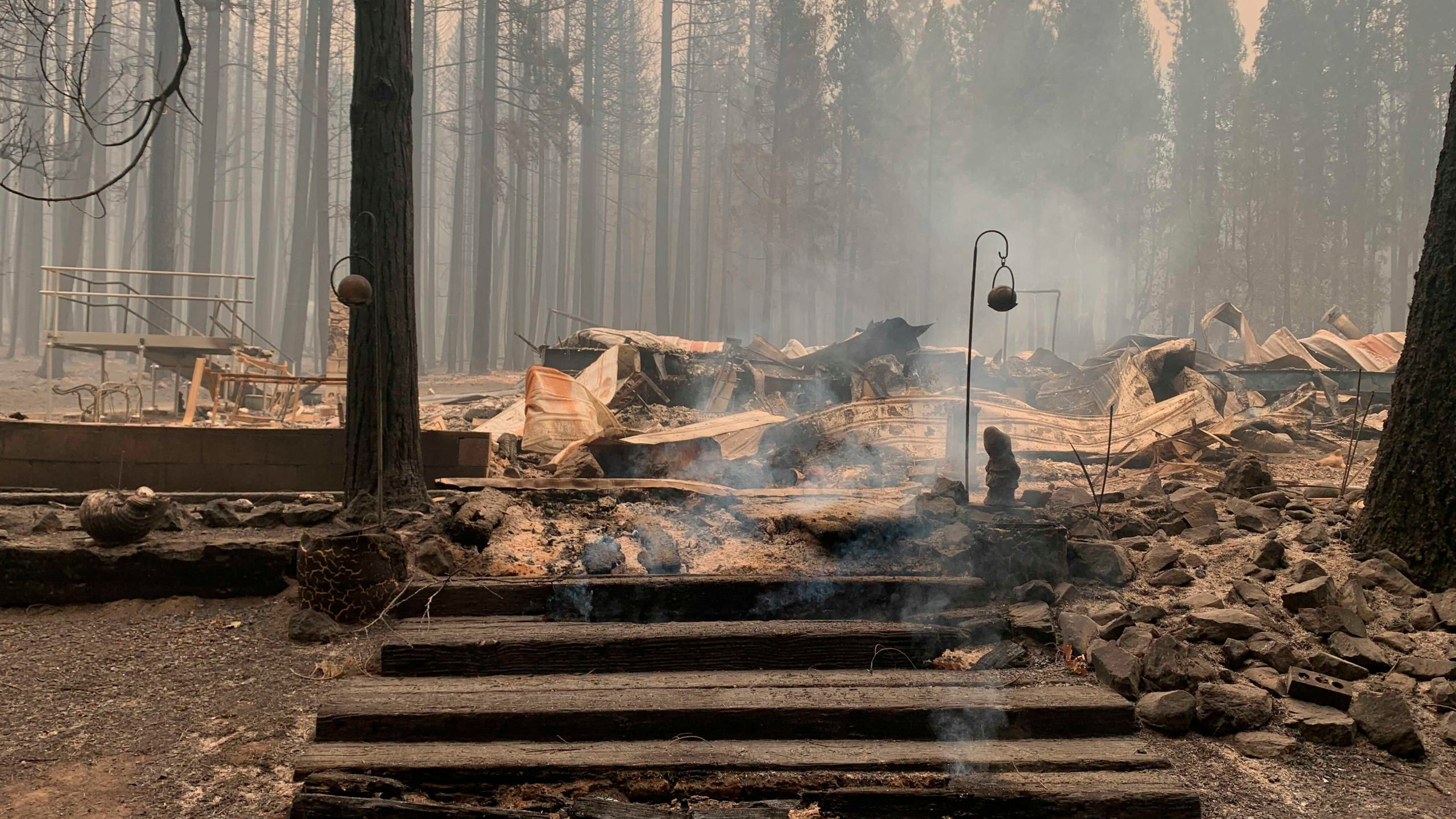 Smoke comes out under the front steps of a house that burned along North Arm Road in Plumas County near Taylorsville, Calif., Sunday, Aug. 15, 2021. (AP Photo/Eugene Garcia)