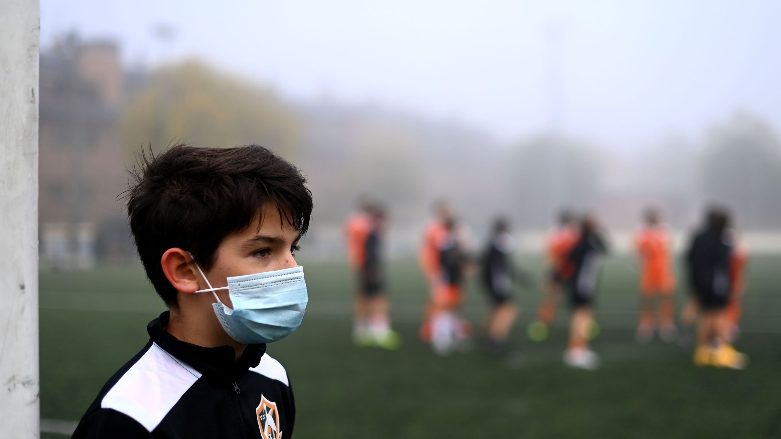 A boy wearing a face mask to protect against the spread of the novel coronavirus attends a football match with his team of Football Player Academy (FPA) Las Rozas in Las Rozas, outside Madrid, on Oct. 24, 2020. (Gabriel Bouys / AFP)