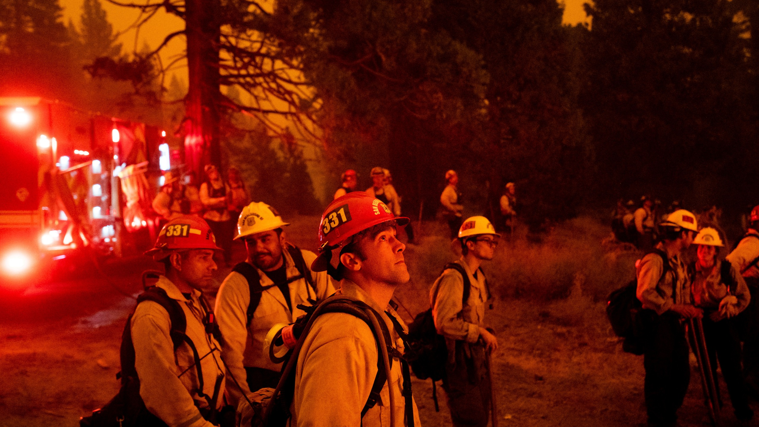 In this Thursday, Aug. 26, 2021 file photo, Capt. Adam Tinker and his crew monitor a firing operation, where crews burn vegetation to create a control line, while battling the Caldor Fire in Eldorado National Forest. (AP Photo/Noah Berger, File)