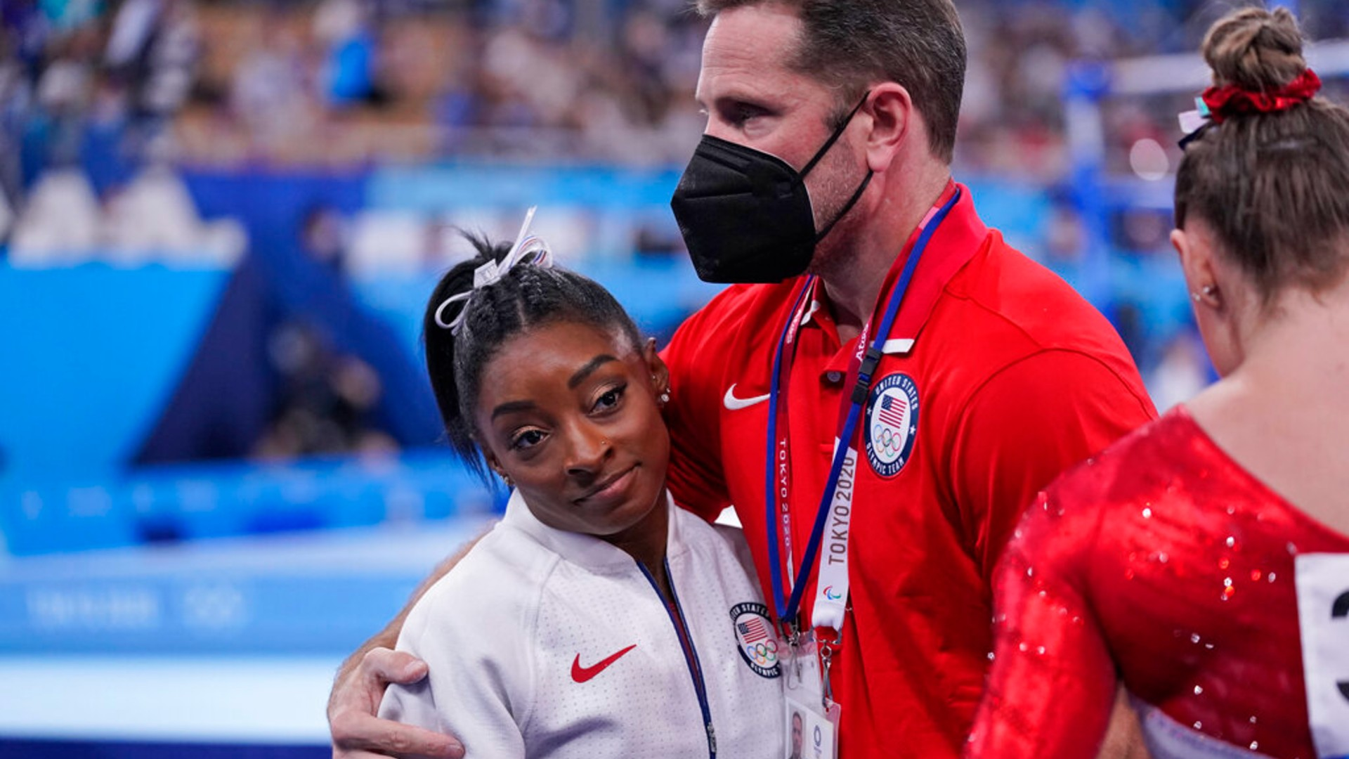 Coach Laurent Landi embraces Simone Biles, after she exited the team final with apparent injury, at the 2020 Summer Olympics, Tuesday, July 27, 2021, in Tokyo. (AP Photo/Gregory Bull)