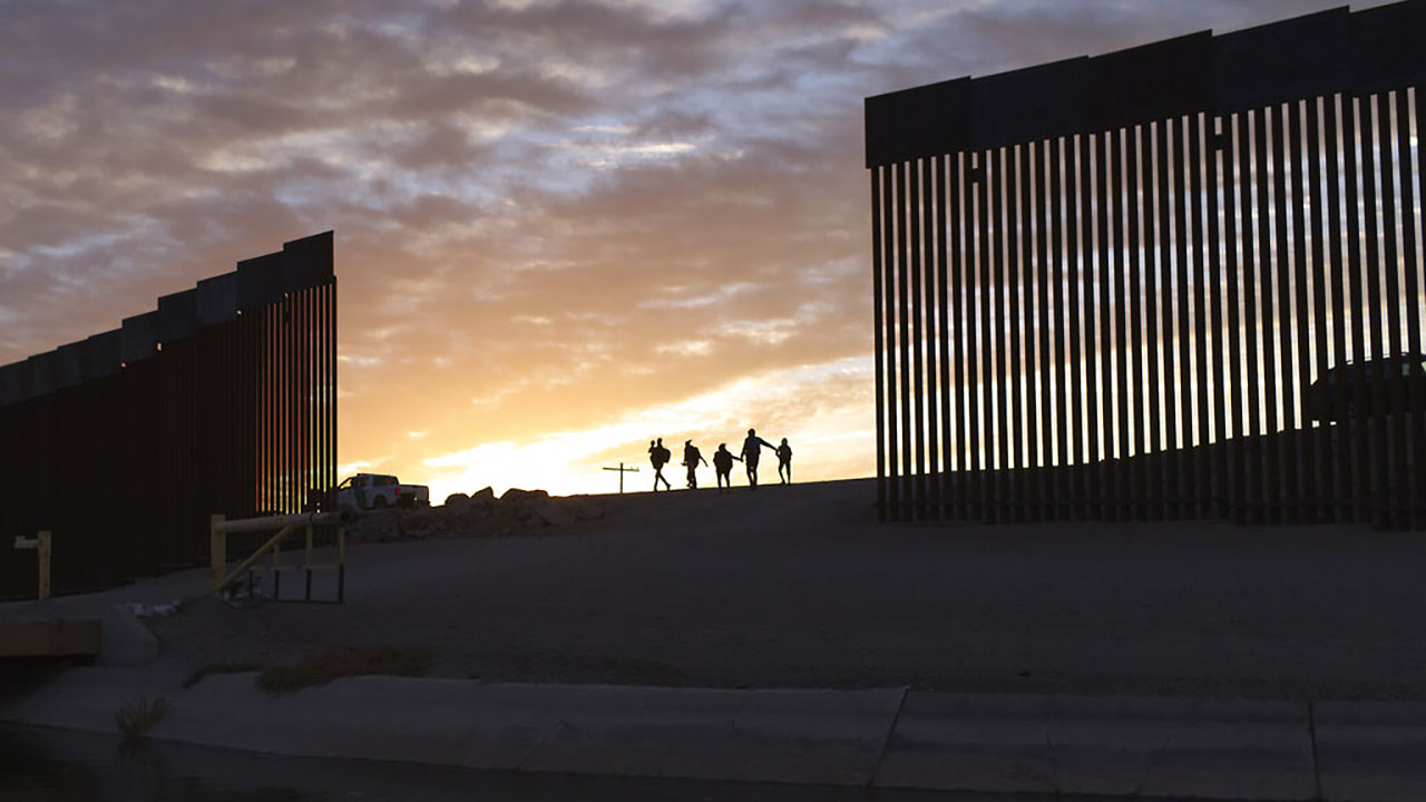 In this June 10, 2021 file photo, a pair of migrant families from Brazil pass through a gap in the border wall to reach the United States after crossing from Mexico to Yuma, Ariz., to seek asylum. (AP Photo/Eugene Garcia, File)