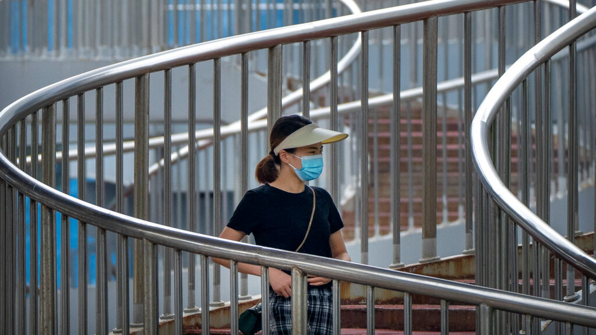 A woman wearing a face mask to protect against COVID-19 walk across a pedestrian bridge during the morning rush hour in Beijing, Wednesday, Aug. 4, 2021. (AP Photo/Mark Schiefelbein)