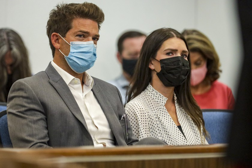 Newport Beach Dr. Grant Robicheaux, and his girlfriend, Cerissa Riley, sit inside a courtroom during a hearing at Orange County Superior Court in Santa Ana on Aug. 19, 2021. (Irfan Khan / Los Angeles Times)