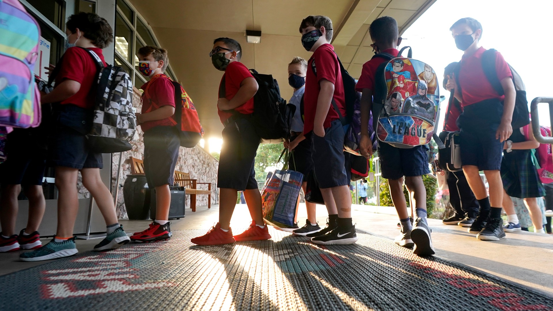 In this Aug. 17, 2021, file photo, wearing masks to prevent the spread of COVID-19, elementary school students line up to enter school for the first day of classes in Richardson, Texas. As COVID-19 cases surge, a majority of Americans say they support mask mandates for students and teachers in K-12 schools, but their views are sharply divided along political lines. (AP Photo/LM Otero, File)