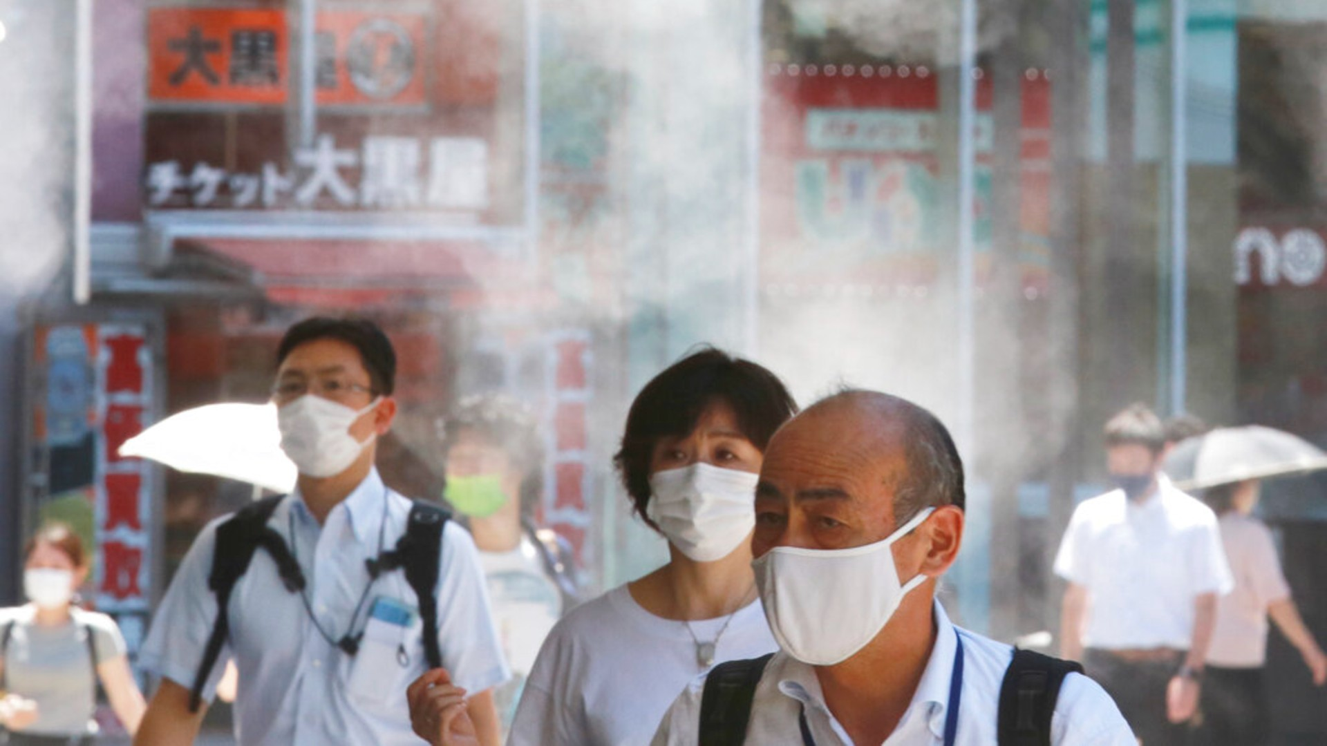 People wearing face masks to protect against the spread of the coronavirus walk under a water mist in Tokyo Thursday, Aug. 5, 2021. (AP Photo/Koji Sasahara)