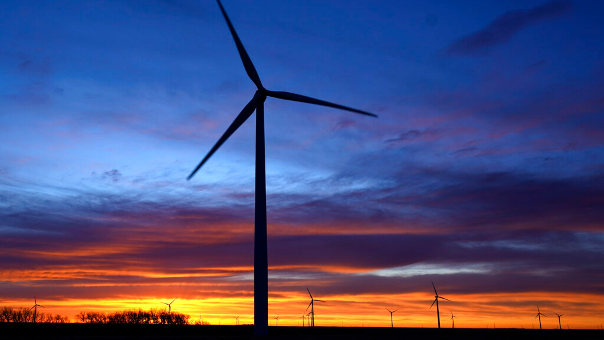 In this Jan. 13, 2021, file photo, wind turbines are silhouetted against the sky at dawn near Spearville, Kan. (AP Photo/Charlie Riedel, File)