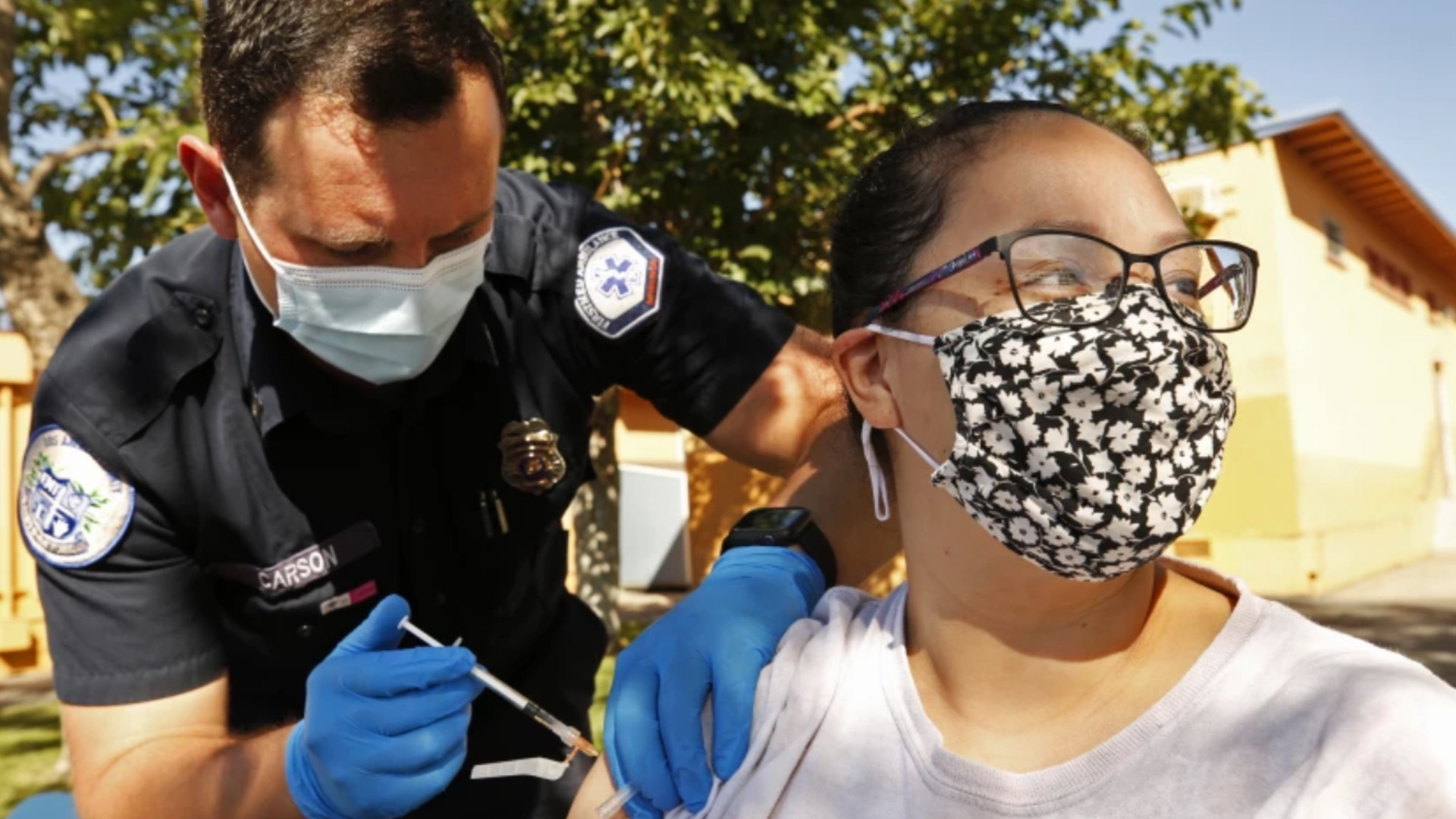 Diana Gomez receives a Pfizer COVID-19 vaccine from Kyle Carson, an EMT with FirstMed Ambulance Services in Arleta.(Al Seib / Los Angeles Times)