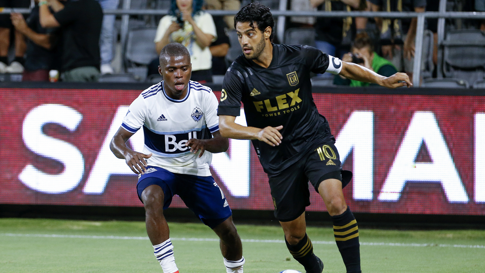 Los Angeles FC forward Carlos Vela drives the ball past Vancouver Whitecaps midfielder Deiber Caicedo during the second half of an MLS soccer match in Los Angeles on July 24, 2021. (Ringo H.W. Chiu/Associated Press)