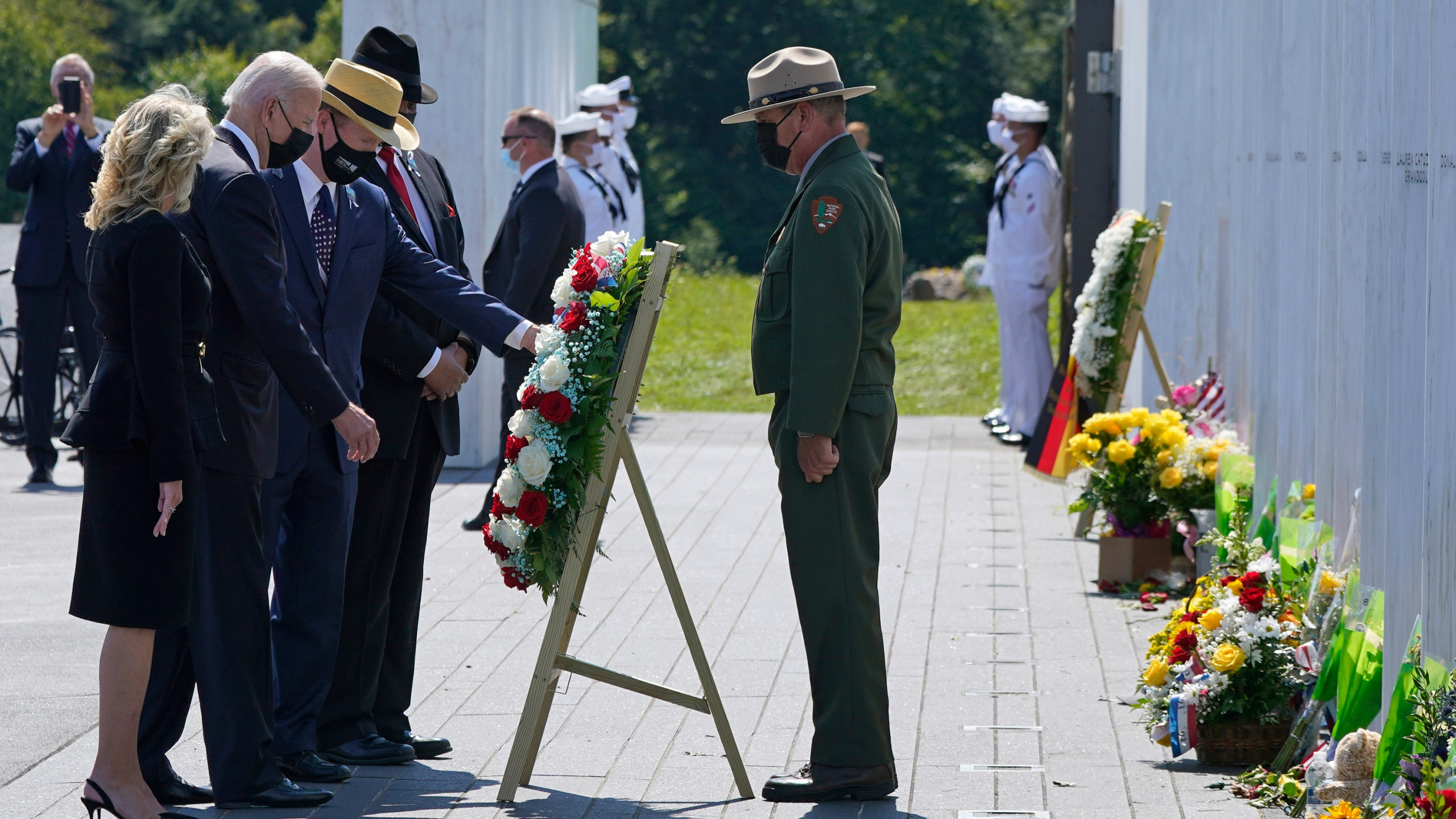 President Joe Biden, second from left, and First Lady Jill Biden, left, help place a wreath at the Wall of Names at the Flight 93 National Memorial with Gordon Felt, third from left, who lost his brother Edward Felt in the crash of Flight 93 in Shanksville, Pa., Saturday, Sept. 11, 2021. (AP Photo/Gene J. Puskar)