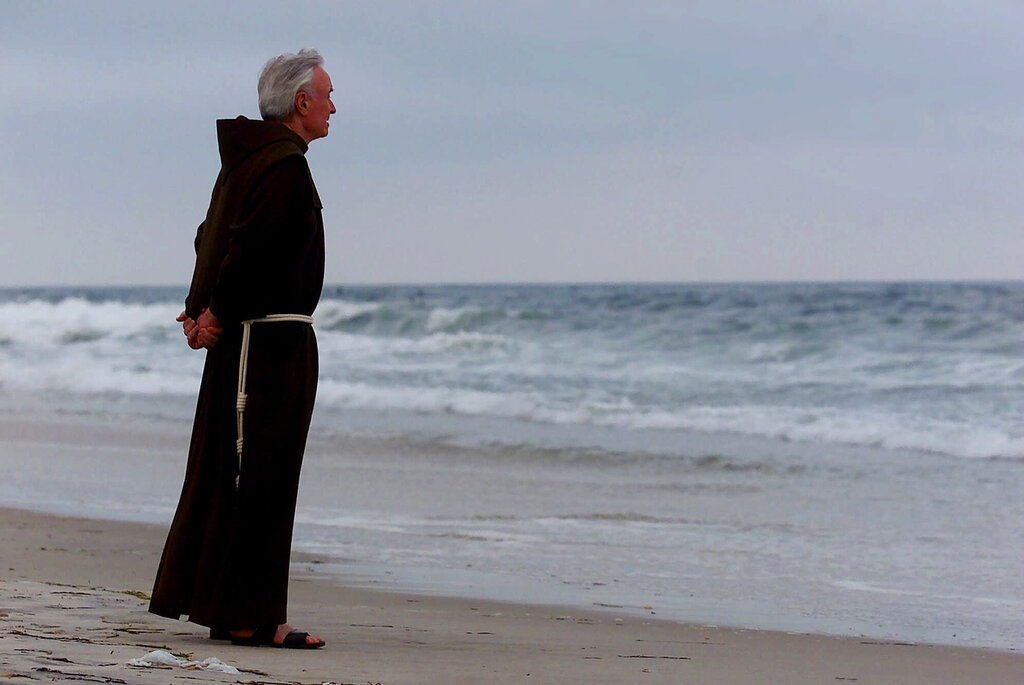 In this July 17, 2000 file photo, Father Mychal Judge, a chaplain with the New York City Fire Department, stands at the shore before a service where 230 candles were lit for the July 17, 1996 victims of TWA Flight 800, at Smith Point Park in Shirley, N.Y. (AP Photo/Ed Betz, File)