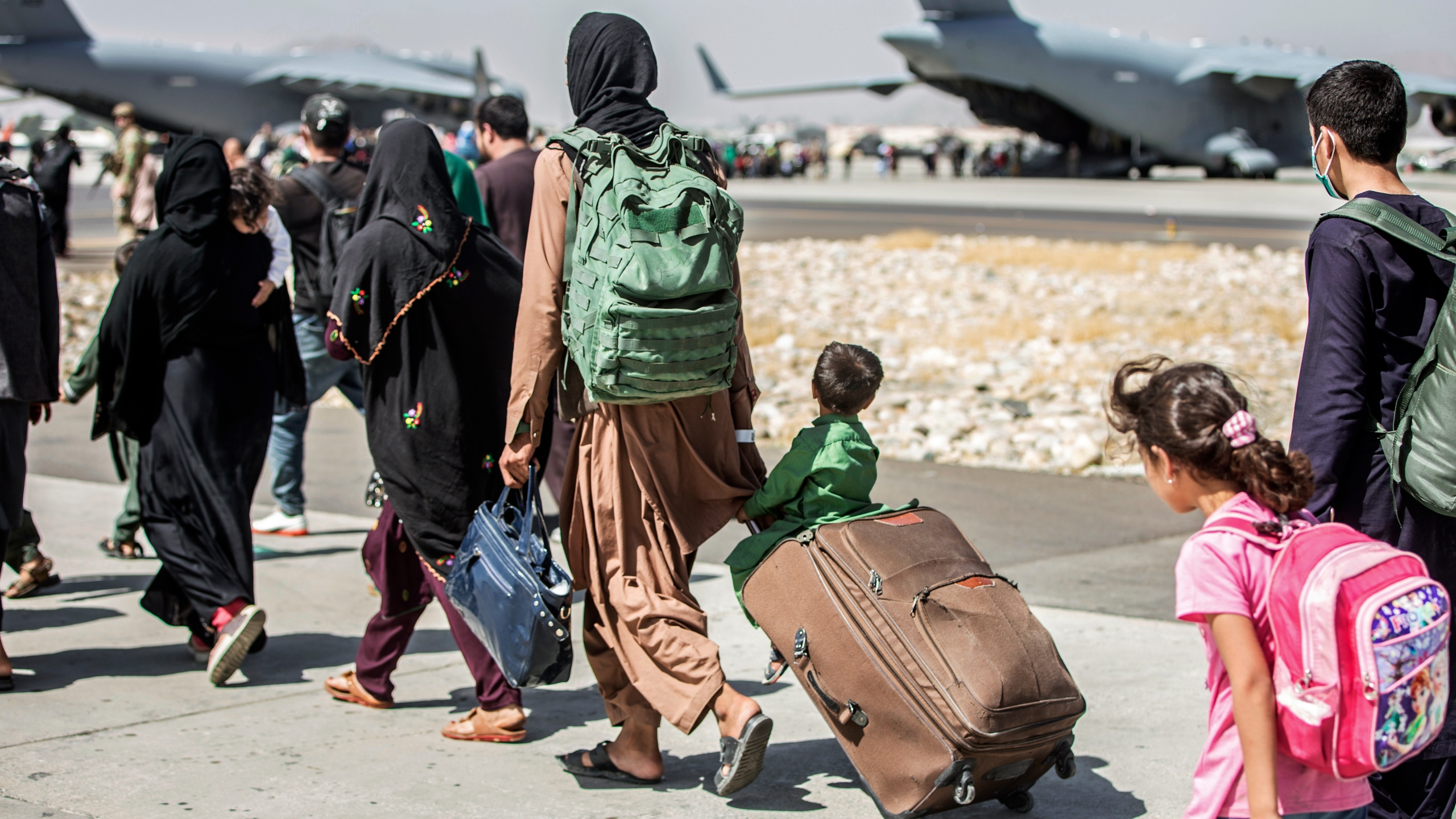 In this Aug. 24, 2021, file photo provided by the U.S. Marine Corps, families walk towards their flight during ongoing evacuations at Hamid Karzai International Airport, in Kabul, Afghanistan. More than 30 California children are stuck in Afghanistan after traveling to the country to see their relatives weeks before the Taliban seized power and US forces left, according to school districts where the kids are enrolled. (Sgt. Samuel Ruiz/U.S. Marine Corps via AP, File)