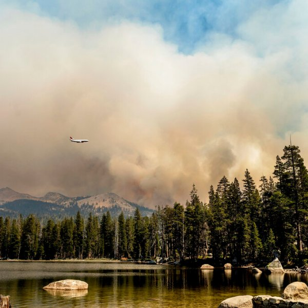 A tanker flies over Wrights Lake while battling the Caldor Fire in Eldorado National Forest, Calif., on Wednesday, Sept. 1, 2021. (AP Photo/Noah Berger)