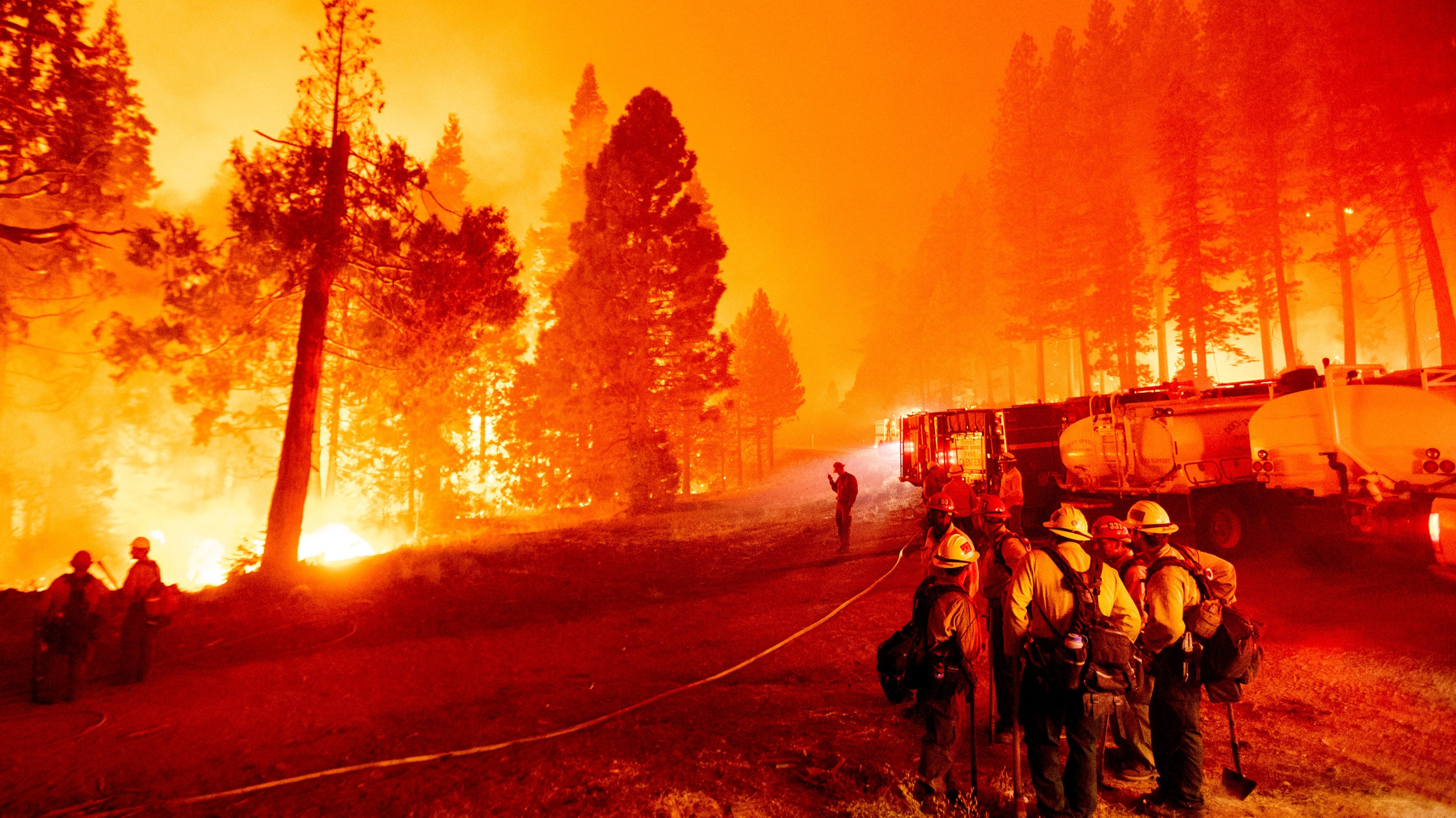 In this Thursday, Aug. 26, 2021 file photo, the Caldor Fire burns along both sides of Highway 50 as firefighters work to stop its eastward spread in Eldorado National Forest, Calif.. Last week, managers overseeing the fight against the massive wildfire scorching California's Lake Tahoe region thought they could have it contained by the start of this week. Instead, on Monday, Aug. 30, 2021, the Caldor Fire crested the Sierra Nevada, forcing the unprecedented evacuation of all 22,000 residents of South Lake Tahoe. (AP Photo/Noah Berger, File)