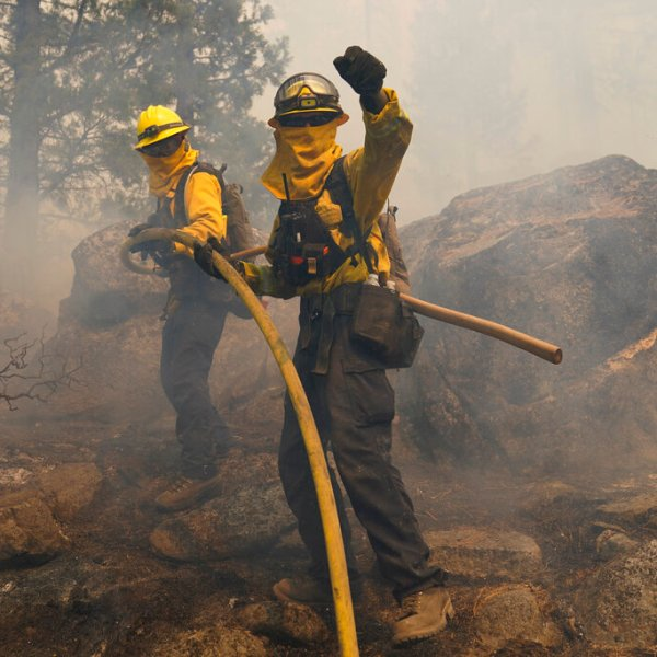 Two firefighters carry a water hose up the hill to extinguish a backfire set to prevent the Caldor Fire from spreading near South Lake Tahoe, Calif., Thursday, Sept. 2, 2021. (AP Photo/Jae C. Hong)