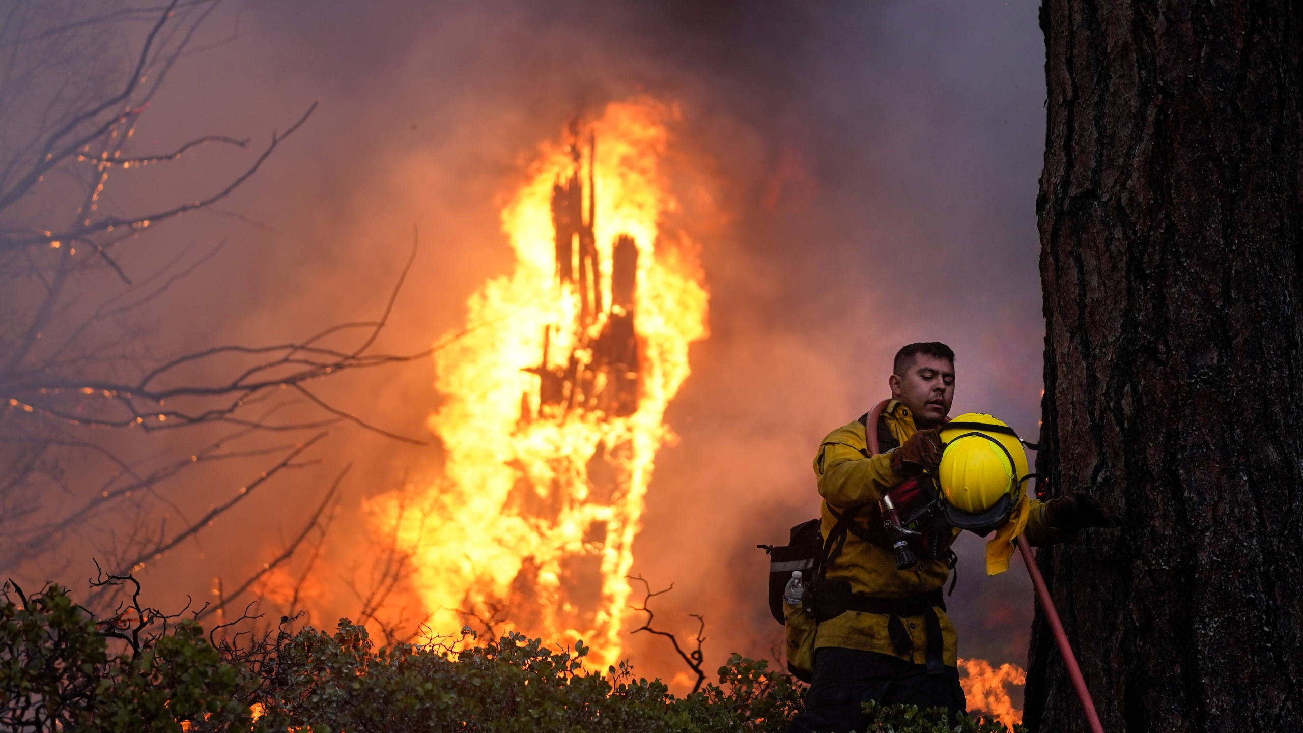 Firefighter Elroy Valadez adjusts his helmet while trying to put out a spot fire from the Caldor Fire burning along Highway 89 near South Lake Tahoe, Calif., Thursday, Sept. 2, 2021. (AP Photo/Jae C. Hong)