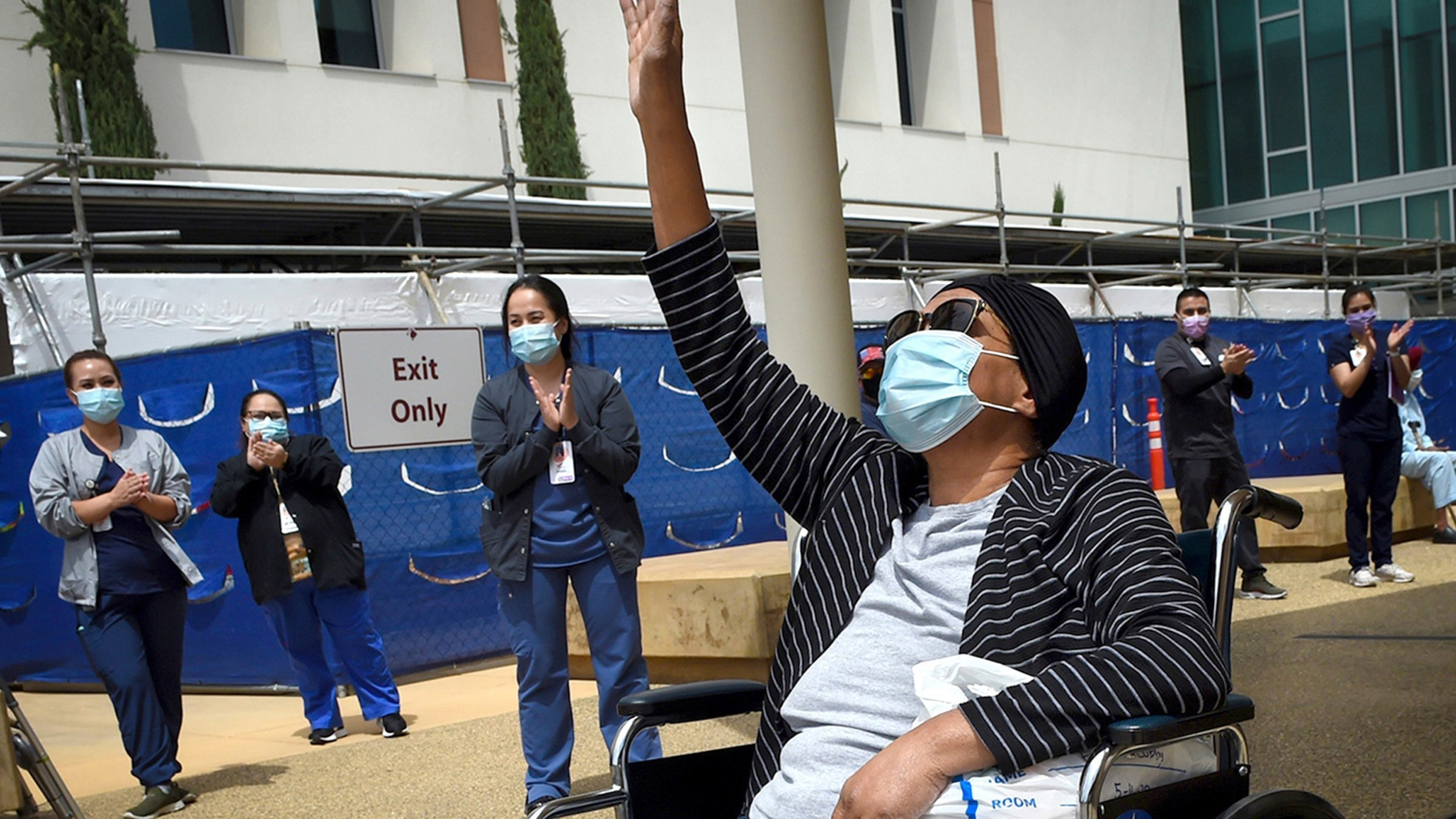 Karen Parker-Bryant, 64, raises a hand skyward after she was released from Clovis Community Hospital in Fresno after a battle with COVID-19 on May 19, 2020. (John Walker / The Fresno Bee via Associated Press)