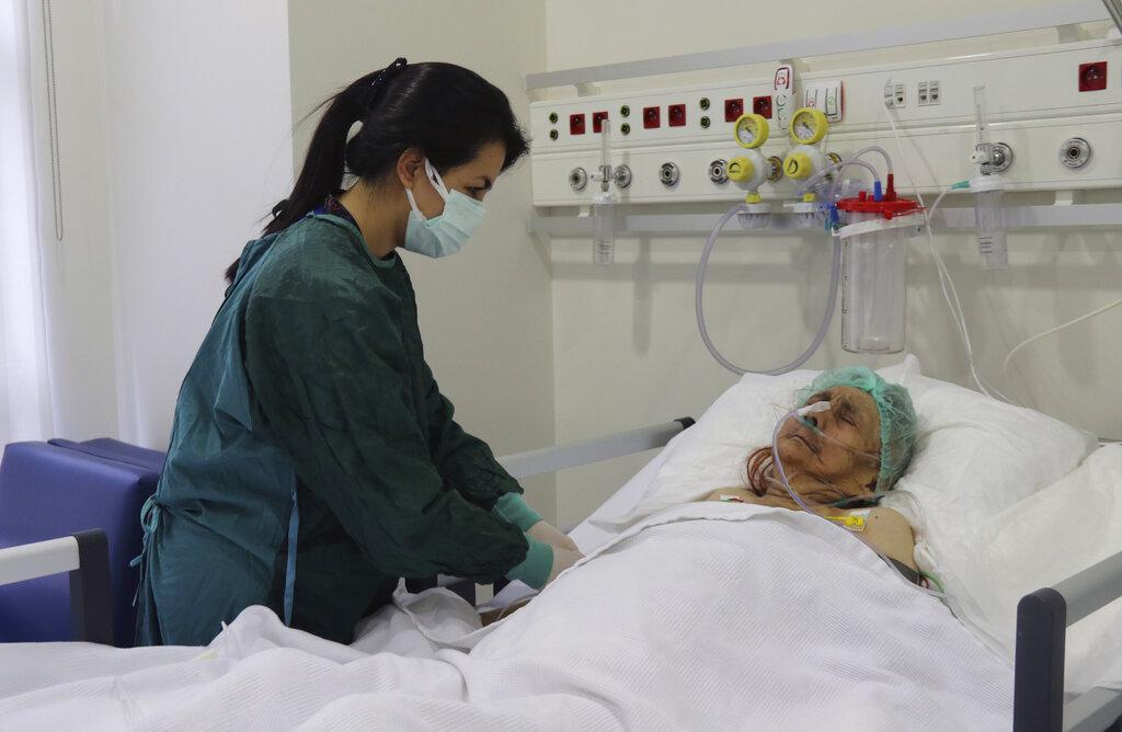 A nurse monitors Ayse Karatay at the City Hospital in Eskisehir, western Turkey, Saturday, Sept. 4, 2021. (IHA via AP)