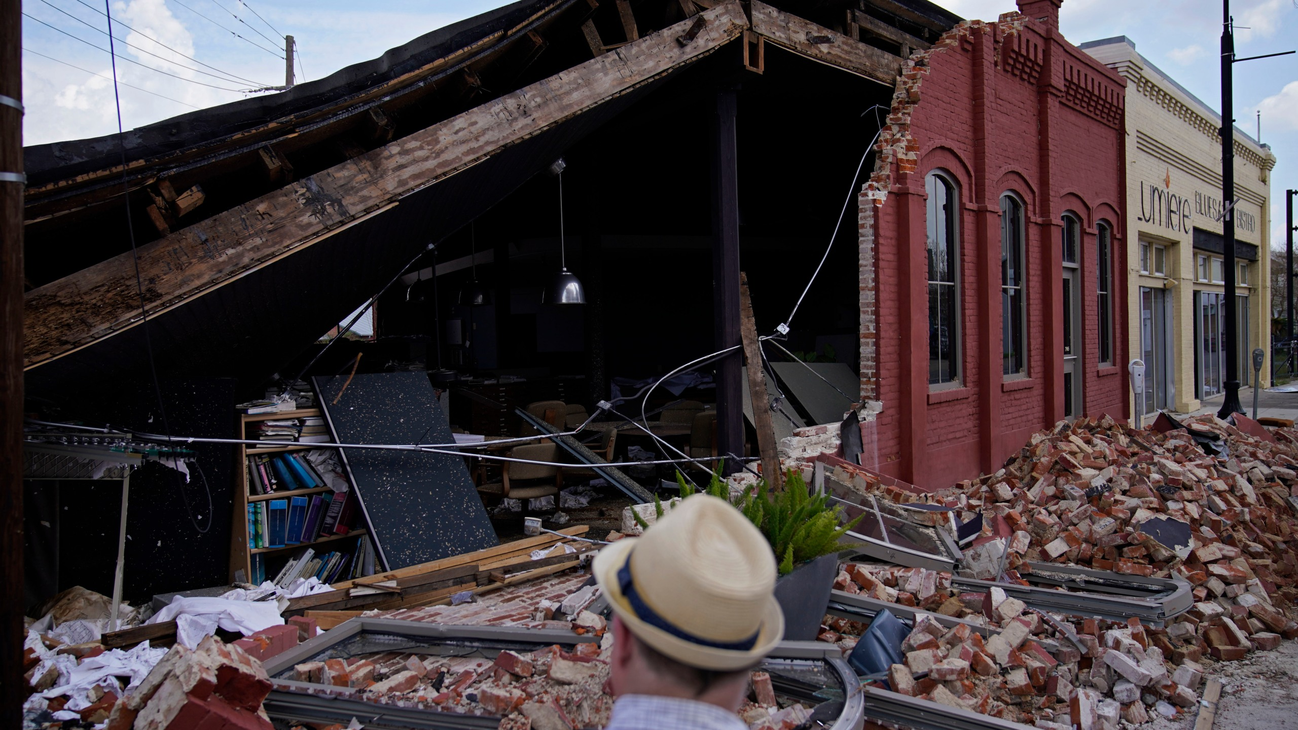 A man looks at a partially collapsed building in the aftermath of Hurricane Ida, Saturday, Sept. 4, 2021, in Houma, La. Full restoration of electricity to some of the hardest-hit areas of Louisiana battered by Hurricane Ida could take until the end of the month, the head of Entergy Louisiana warned Saturday. (AP Photo/John Locher)