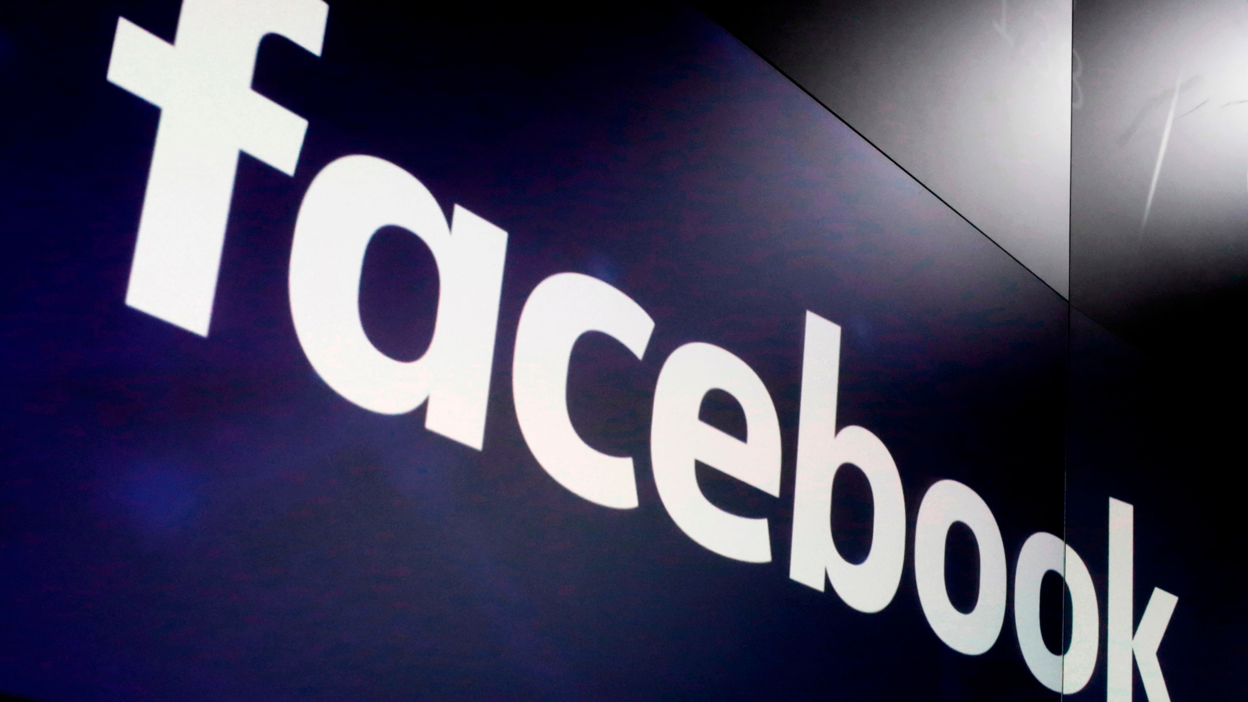 """In this March 29, 2018, file photo, the logo for Facebook appears on screens at the Nasdaq MarketSite in New York's Times Square. Facebook has apologized for putting a """"primates"""" label on a video of Black men, in June 2021, according to a report in the New York Times. (AP Photo/Richard Drew, File)"""