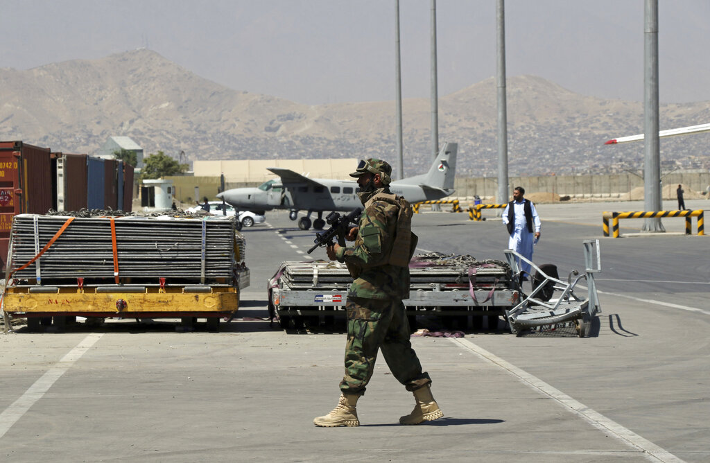 A Taliban soldier walks on the tarmac at Hamid Karzai International Airport in Kabul, Afghanistan, Sunday, Sept. 5, 2021. (AP Photo/Wali Sabawoon)