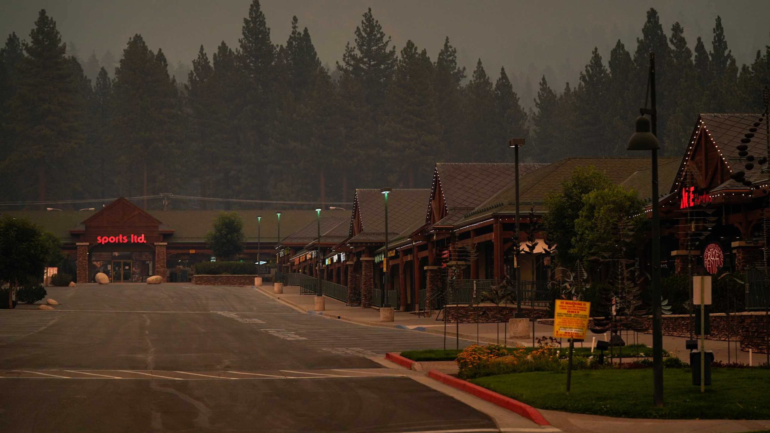 In this Tuesday, Aug. 31, 2021, file photo, a shopping mall is empty after a mandatory evacuation was ordered due to the Caldor Fire in South Lake Tahoe, Calif. State fire officials said evacuation orders for the area were reduced to warnings as of 3 p.m. on Sunday, Sept. 5. Some 22,000 people had been forced to flee the popular resort and nearby areas last week as the Caldor Fire roared toward it. (AP Photo/Jae C. Hong, File)