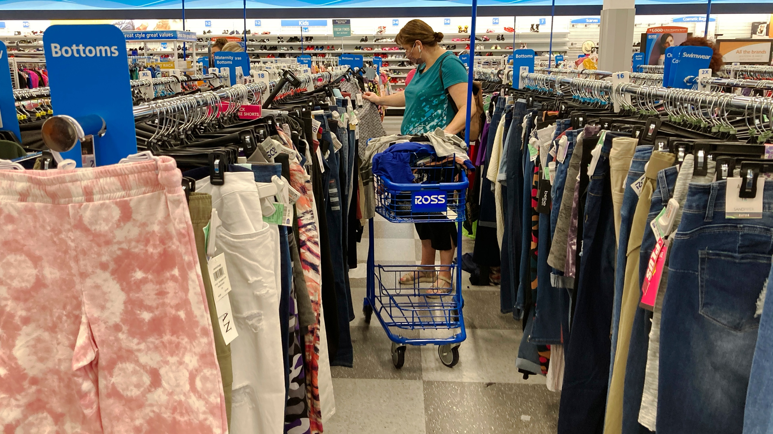 A consumer shops as she wears a mask at a retail store in Morton Grove, Ill., Wednesday, July 21, 2021. With fewer pandemic-related restrictions this year, the option to do more can result in the urge to spend. (AP Photo/Nam Y. Huh)