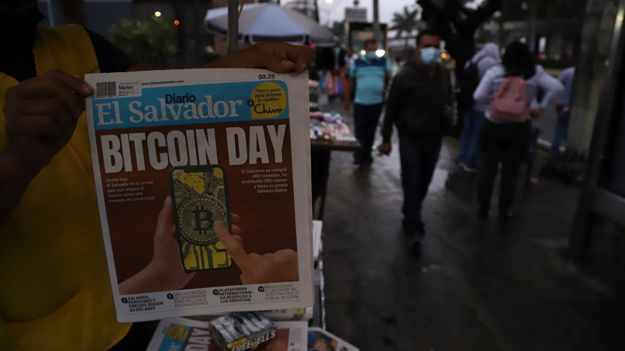 """A newspaper vendor shows the front page of a state-run newspaper carrying the headline """"Bitcoin Day"""" in San Salvador, El Salvador on Sept. 7, 2021. (Salvador Melendez/Associated Press)"""