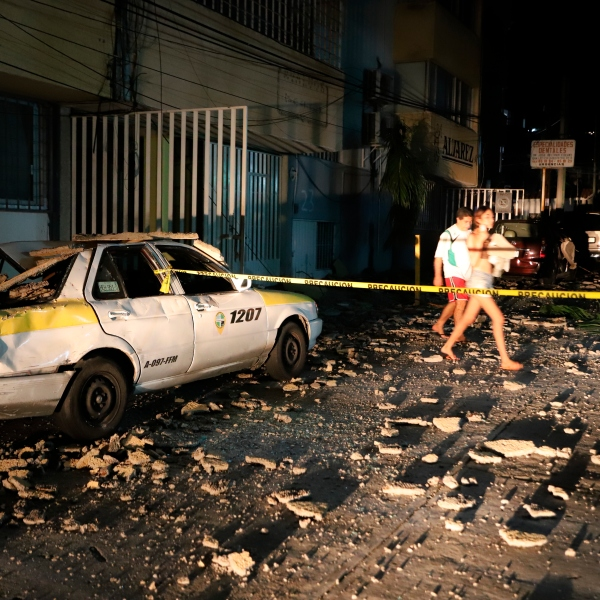 A couple walks past a taxi cab that was damaged by falling debris after a strong earthquake in Acapulco, Mexico, on Sept. 7, 2021. The quake struck southern Mexico near the resort of Acapulco, causing buildings to rock and sway in Mexico City nearly 200 miles away. (Bernardino Hernandez / Associated Press)