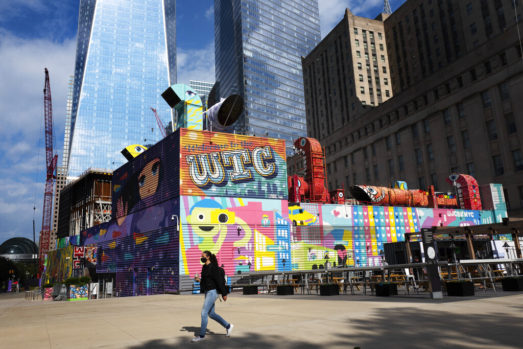 A woman walks by the colorful murals that surround the foundation for 2 World Trade Center, Wednesday, Sept. 8, 2021 in New York. (AP Photo/Mark Lennihan)
