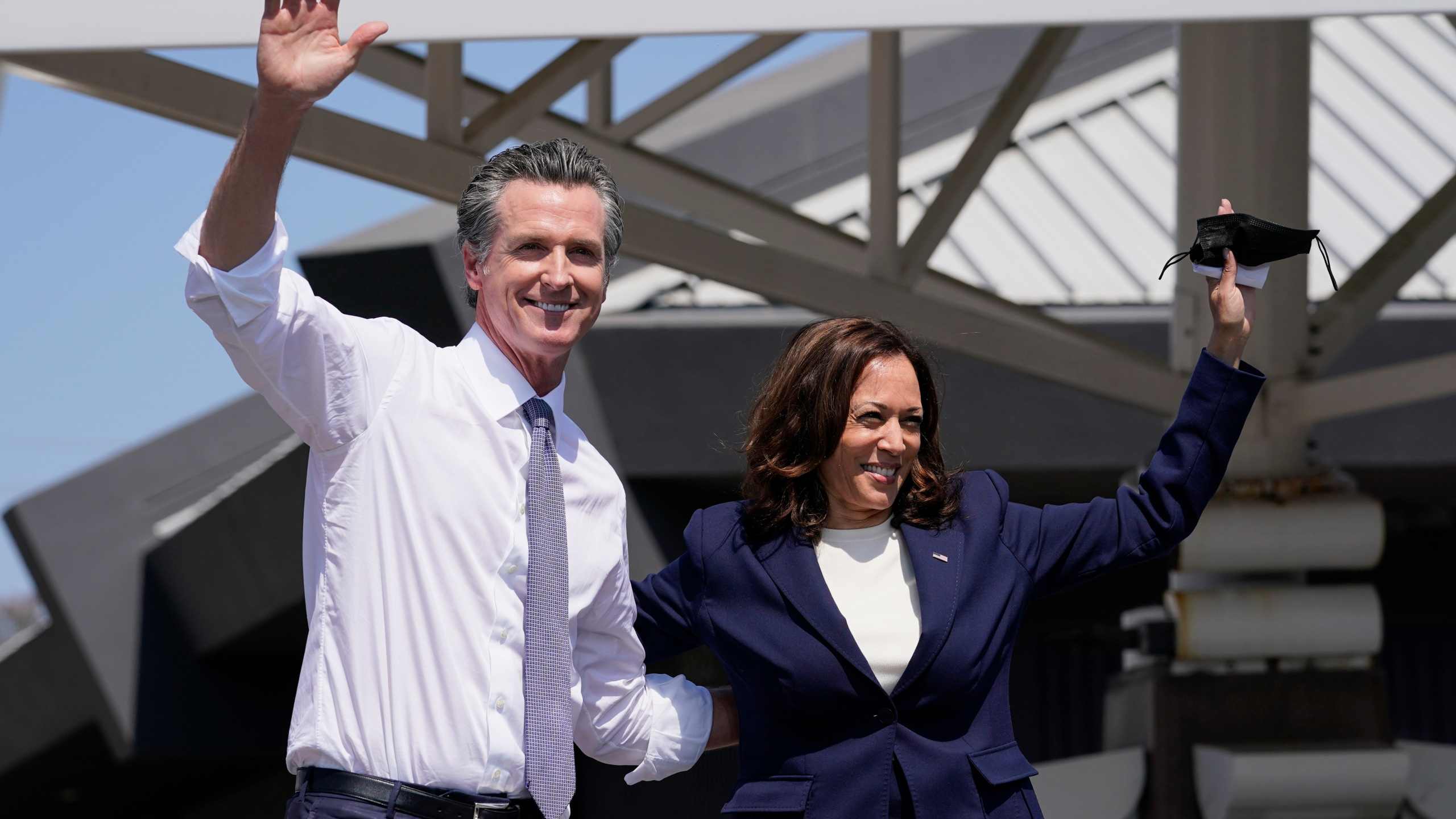 California Gov. Gavin Newsom and Vice President Kamala Harris wave during a campaign event at the IBEW-NECA Joint Apprenticeship Training Center in San Leandro, Calif. on Sept. 8, 2021. (AP Photo/Carolyn Kaster)