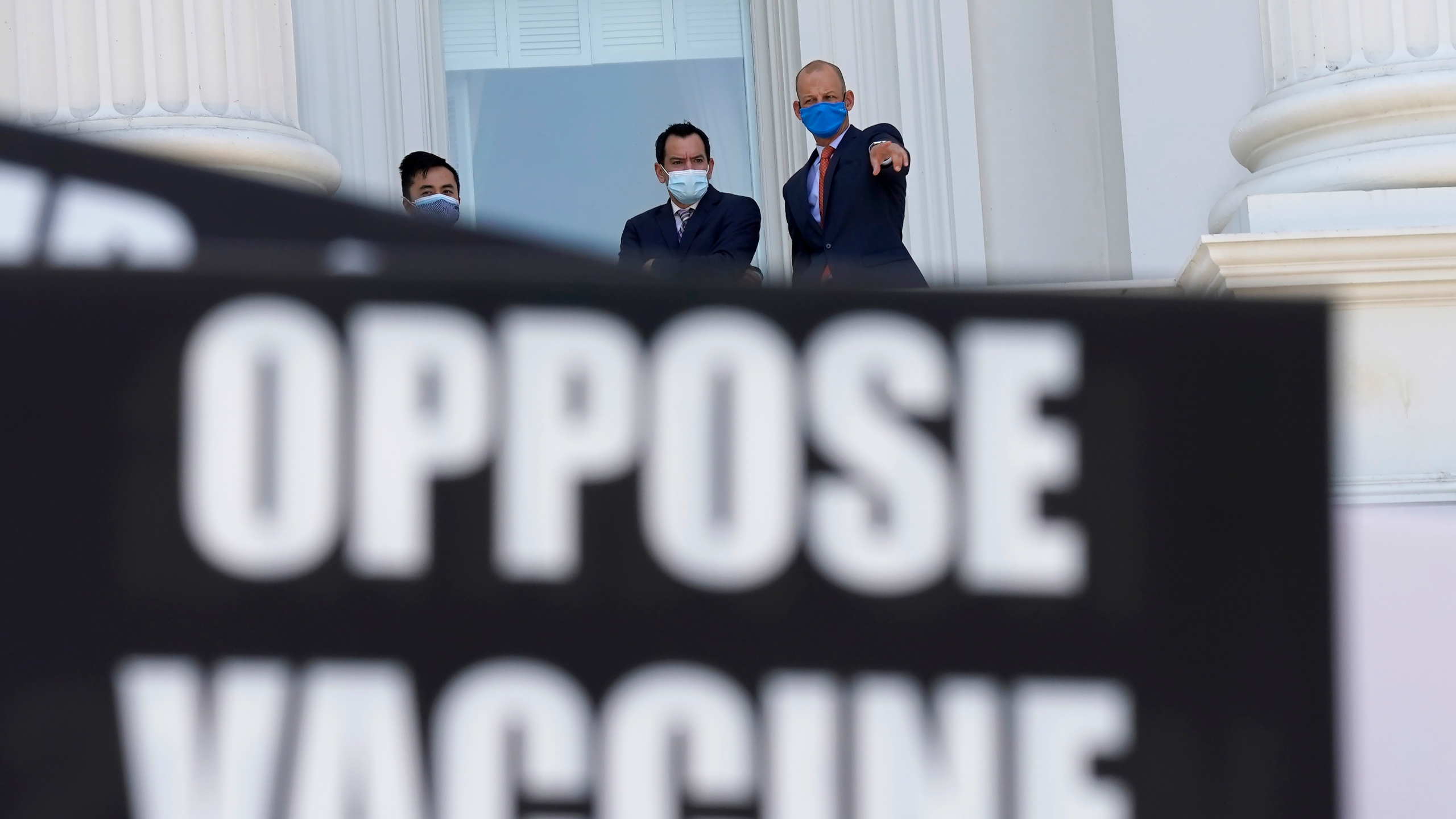 Assembly Speaker Anthony Rendon, of Lakewood, center, and Assemblyman Kevin McCarty, D-Sacramento, right, watch from the balcony outside the Assembly Chambers as protesters opposing vaccine mandates gather at the Capitol in Sacramento. (Rich Pedroncelli/Associated Press)