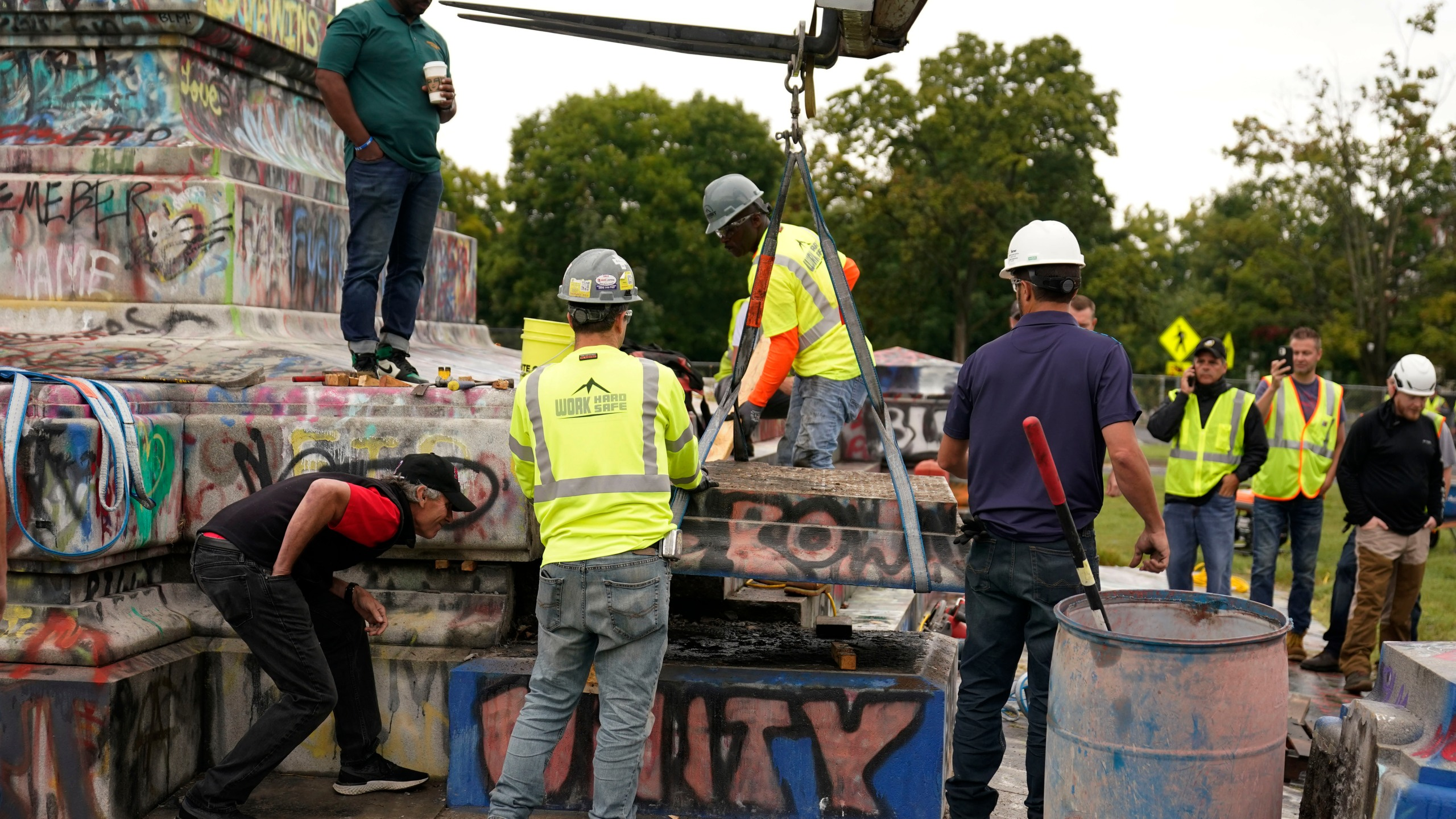Crews move a section of the base as they attempt to locate a time capsule said to be buried in the base of the statue of on Monument Avenue in Richmond, Va., Thursday, Sept. 9, 2021. The statue was removed from the pedestal on Wednesday. (AP Photo/Steve Helber)