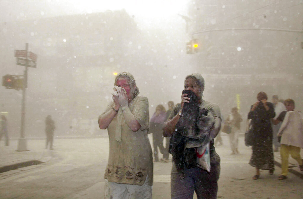 In this Sept. 11, 2001 file photo, people covered in dust from the collapsed World Trade Center buildings, walk through the area, in New York. (AP Photo/Suzanne Plunkett, File)