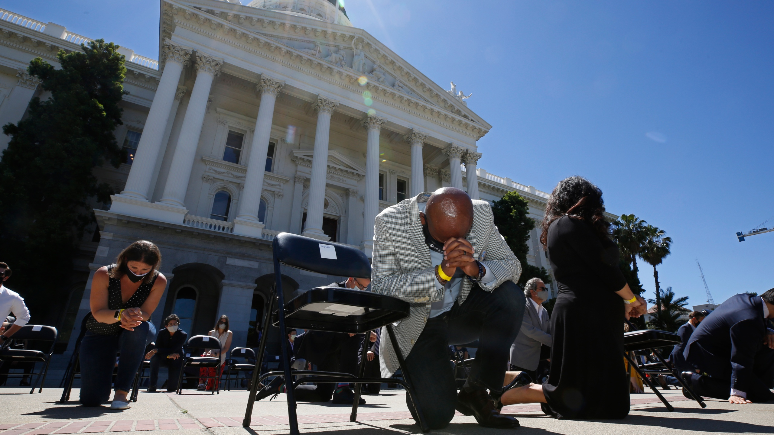 """In this June 9, 2020, file photo, Assemblyman Mike Gipson, D-Carson, bows his head as he and other members of the California Legislature kneel to honor George Floyd at the Capitol in Sacramento, Calif. Lawmakers approved, Thursday, Sept. 9, 2021, Gipson's measure that would prohibit police from using techniques that create a substantial risk of what's known as """"positional asphyxia."""" (AP Photo/Rich Pedroncelli, File)"""
