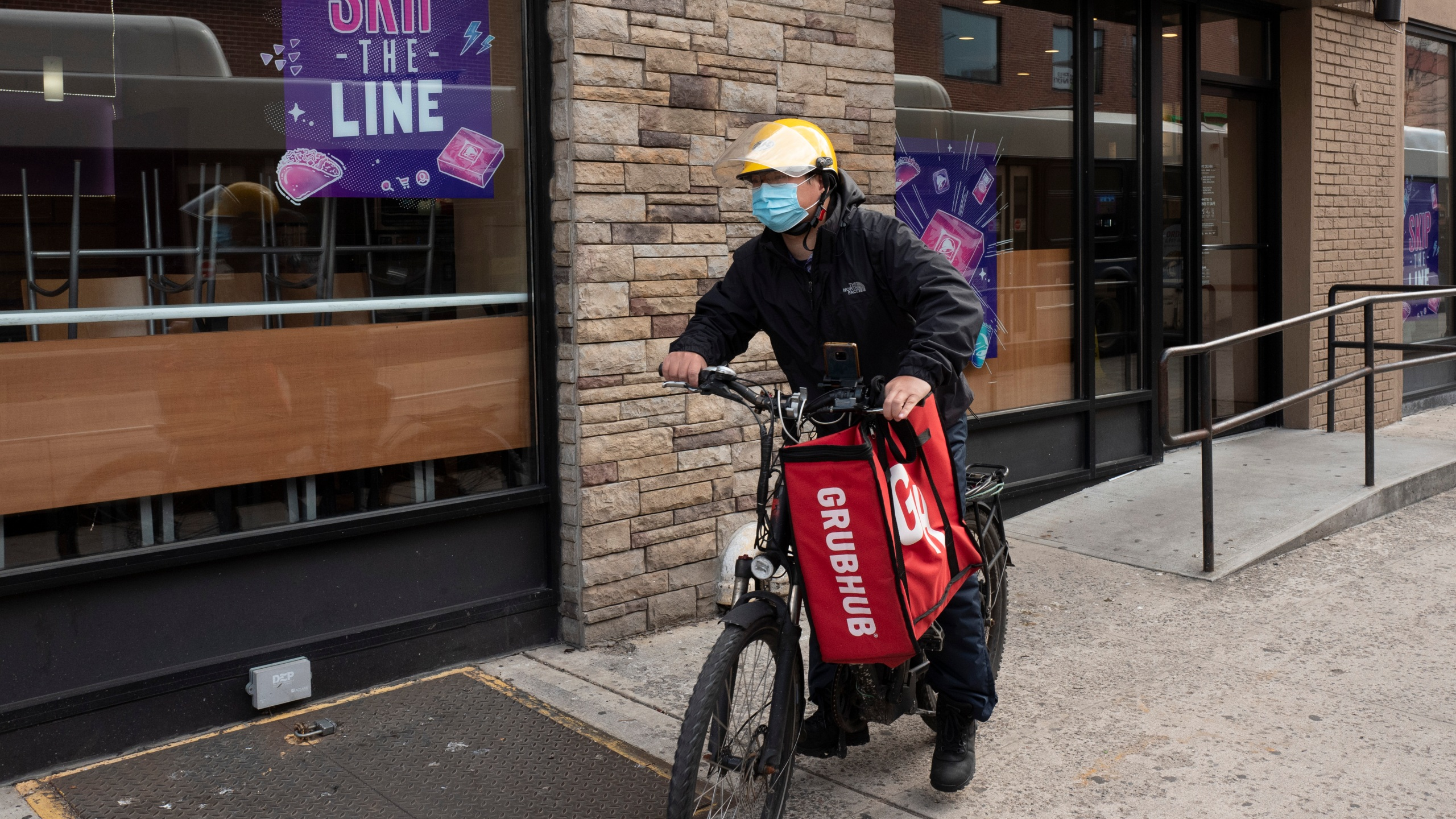 In this April 21, 2021, file photo, a delivery man bikes with a food bag from Grubhub in New York. (AP Photo/Mark Lennihan, File)