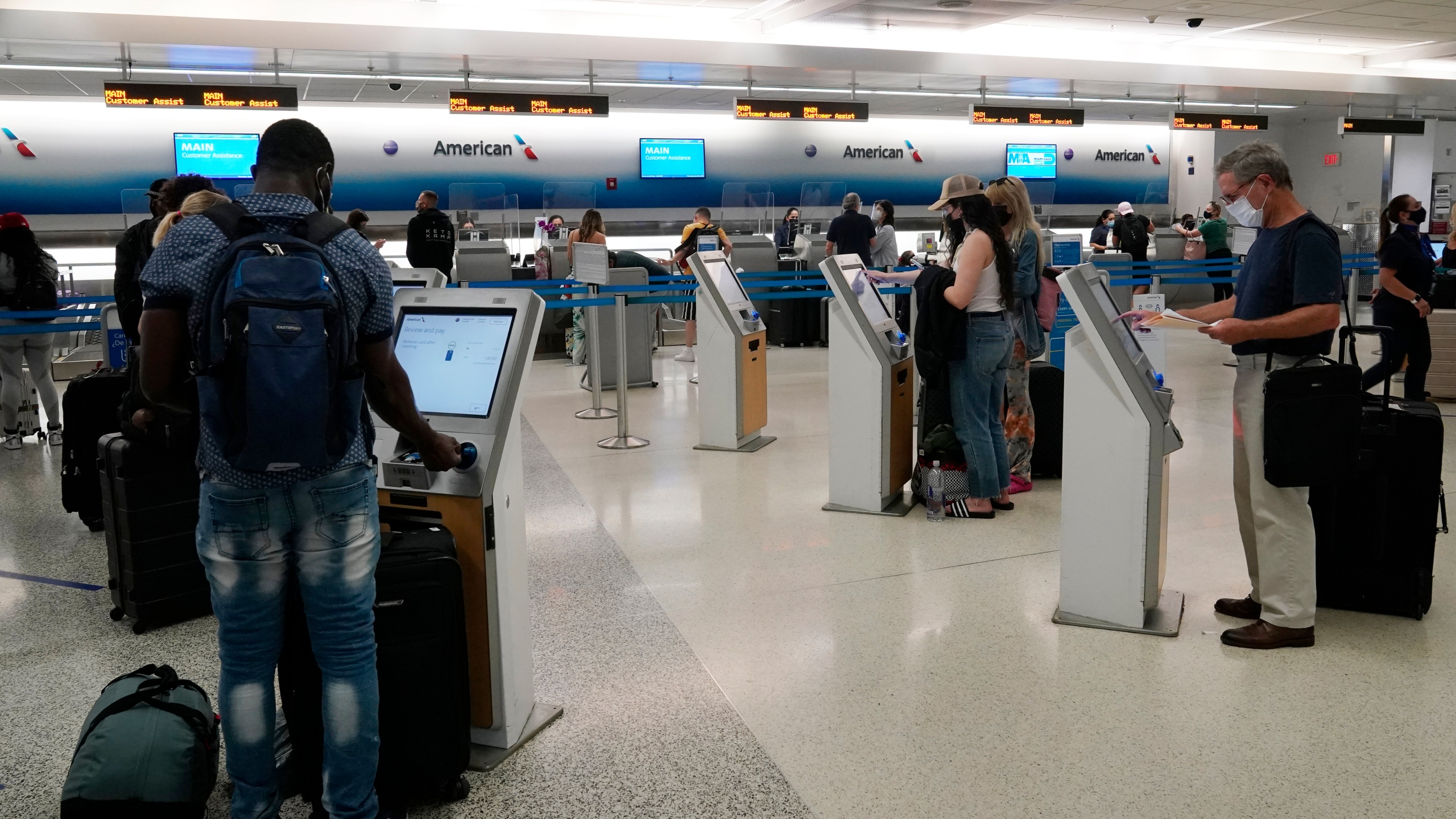In this April 29, 2021 photo, travelers use the self-service kiosk to check in and pay for luggage at the American Airlines terminal in Miami. The Transportation Department is detailing efforts it's making to help airline customers who didn't get refunds after their flights were canceled during the early days of the pandemic last year. The department says, Friday, Sept. 10, in a new report that it investigated 20 airlines over failures to issue prompt refunds to customers, and 18 of those probes are still going on.(AP Photo/Marta Lavandier)
