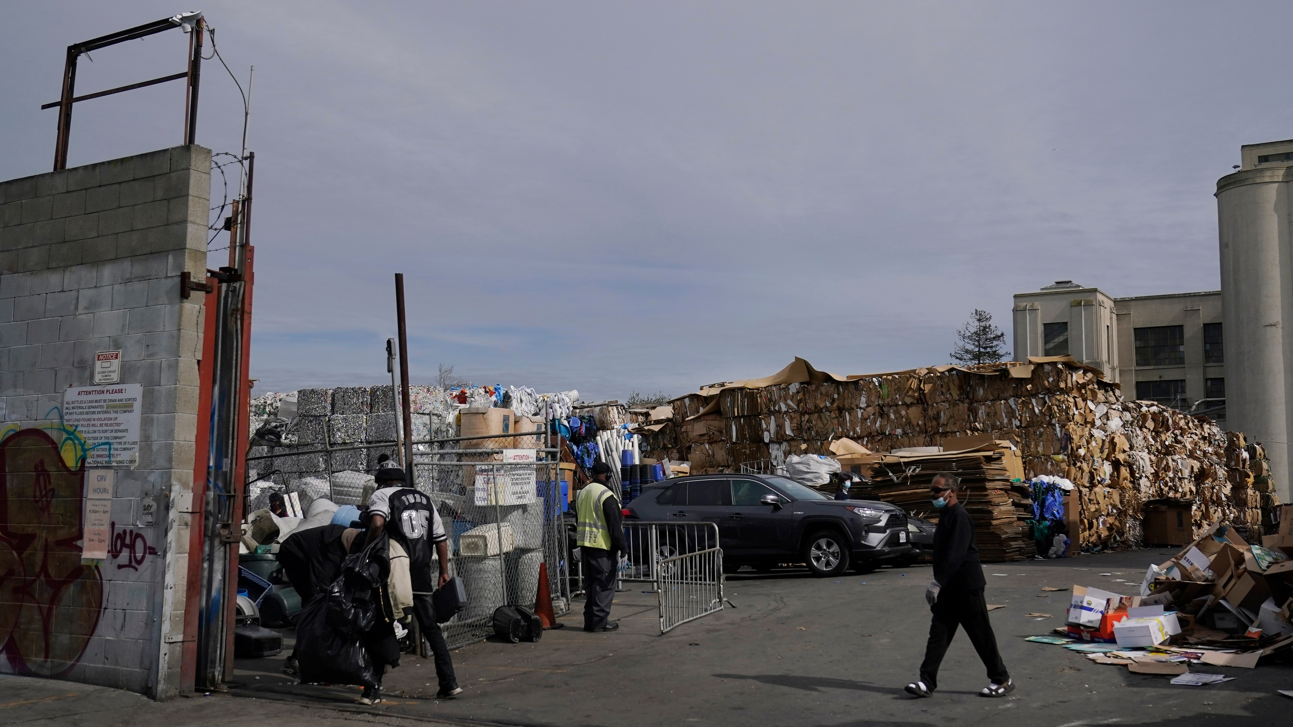 In this Feb. 18, 2021, file photo, people walk inside a recycling location in Oakland, Calif. California lawmakers have approved what advocacy groups say are the nation's strongest protections against falsely labeling items as recyclable when they in fact are destined for landfills. (AP Photo/Jeff Chiu, File)