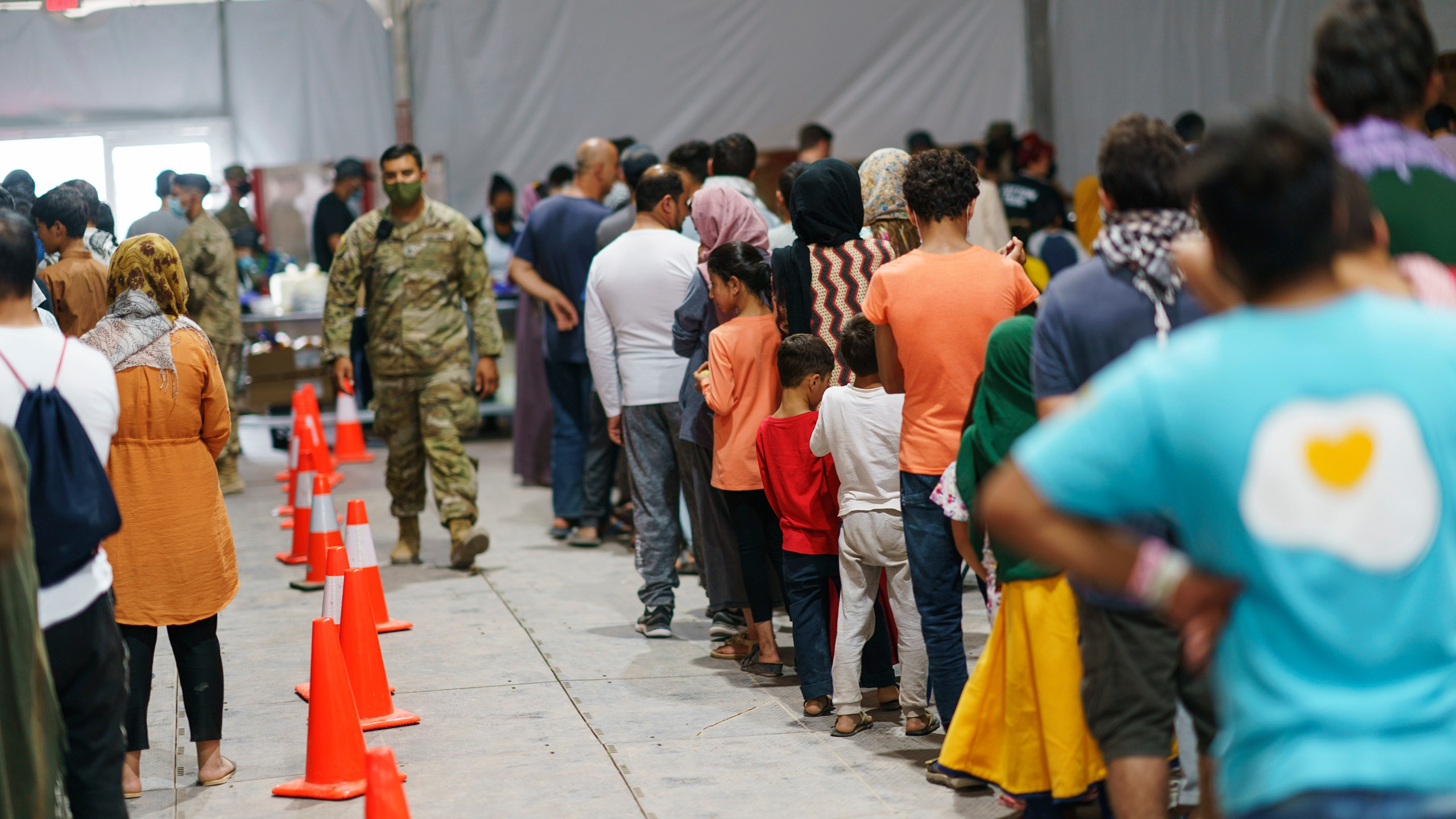 Afghan refugees line up for food in a dining hall at Fort Bliss' Doña Ana Village, in New Mexico, where they are being housed, on Sept. 10, 2021. (David Goldman / Associated Press)