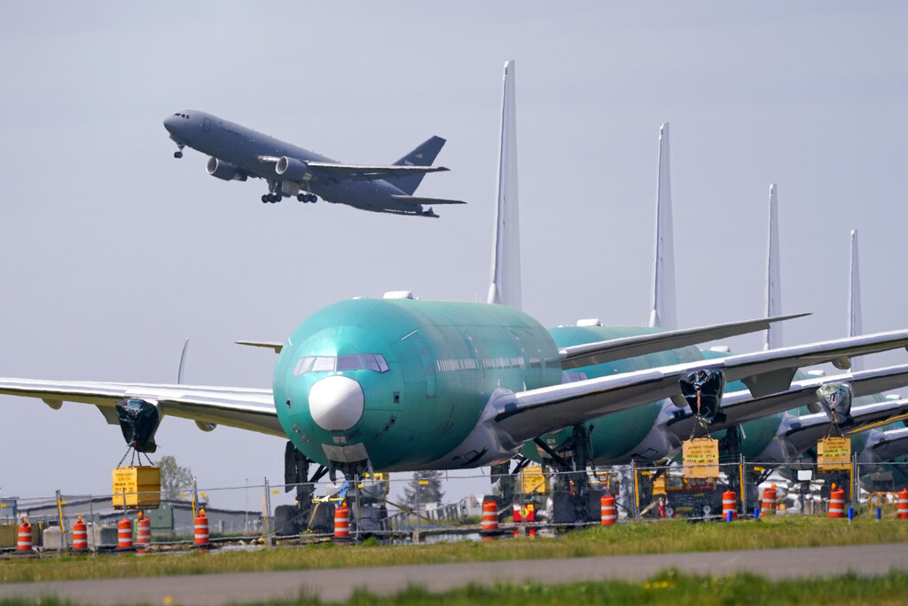 In this April 23, 2021 file photo, A U.S. Air Force KC-46A Pegasus jet takes off in view of a line of Boeing 777X jets parked nose to tail on an unused runway at Paine Field, near Boeing's massive production facility in Everett, Washington. (AP Photo/Elaine Thompson, File)
