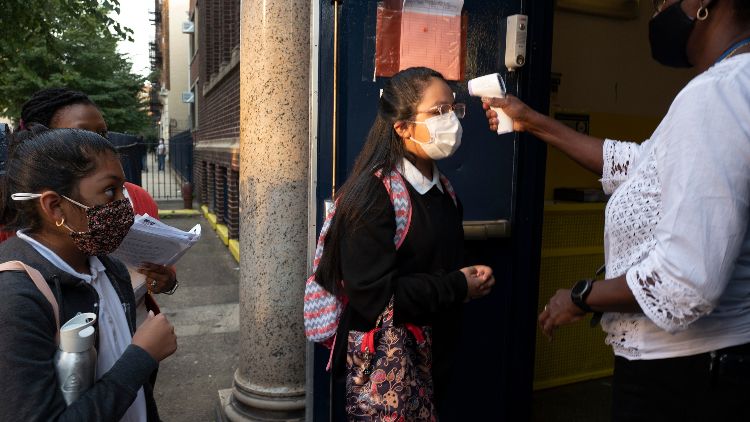 A girl has her temperature checked as she arrives for the first day of school at Brooklyn's PS 245 elementary school on Sept. 13, 2021, in New York. (Mark Lennihan/Associated Press)