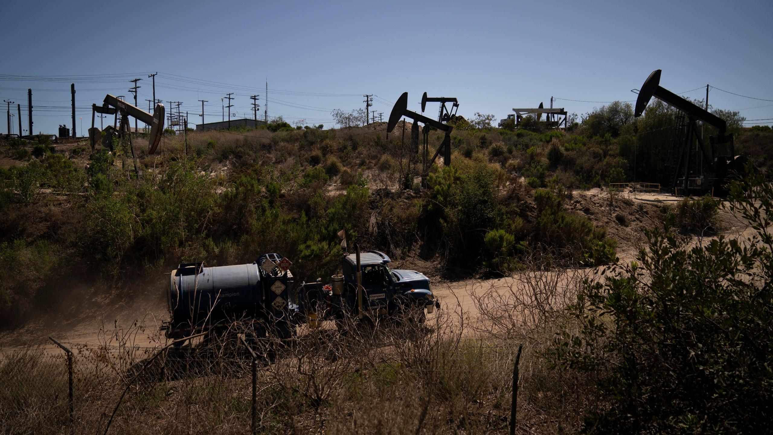 A truck drives past pump jacks operating at the Inglewood Oil Field on June 10, 2021, in Los Angeles. (AP Photo/Jae C. Hong)