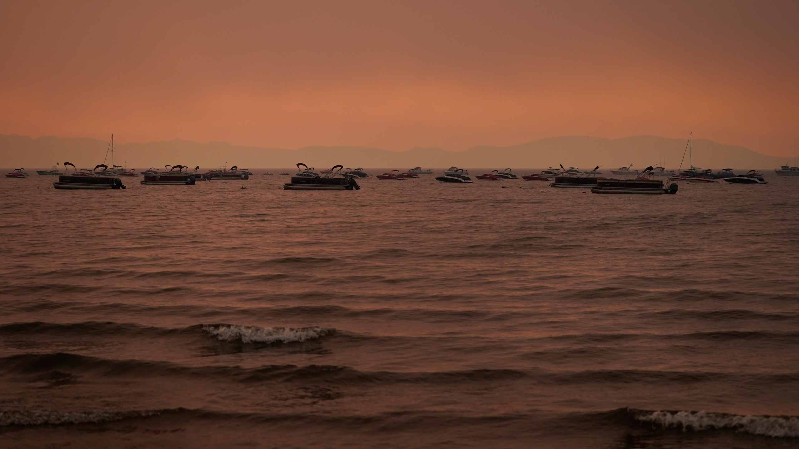 Boats float in the water away from a dock in South Lake Tahoe, Calif., as the Caldor Fire approaches on Aug. 31, 2021. (Jae C. Hong / Associated Press)