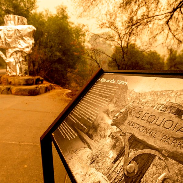 Fire-resistant wrap covers a historic welcome sign as the KNP Complex Fire burns in Sequoia National Park, Calif., on Wednesday, Sept. 15, 2021. (AP Photo/Noah Berger)